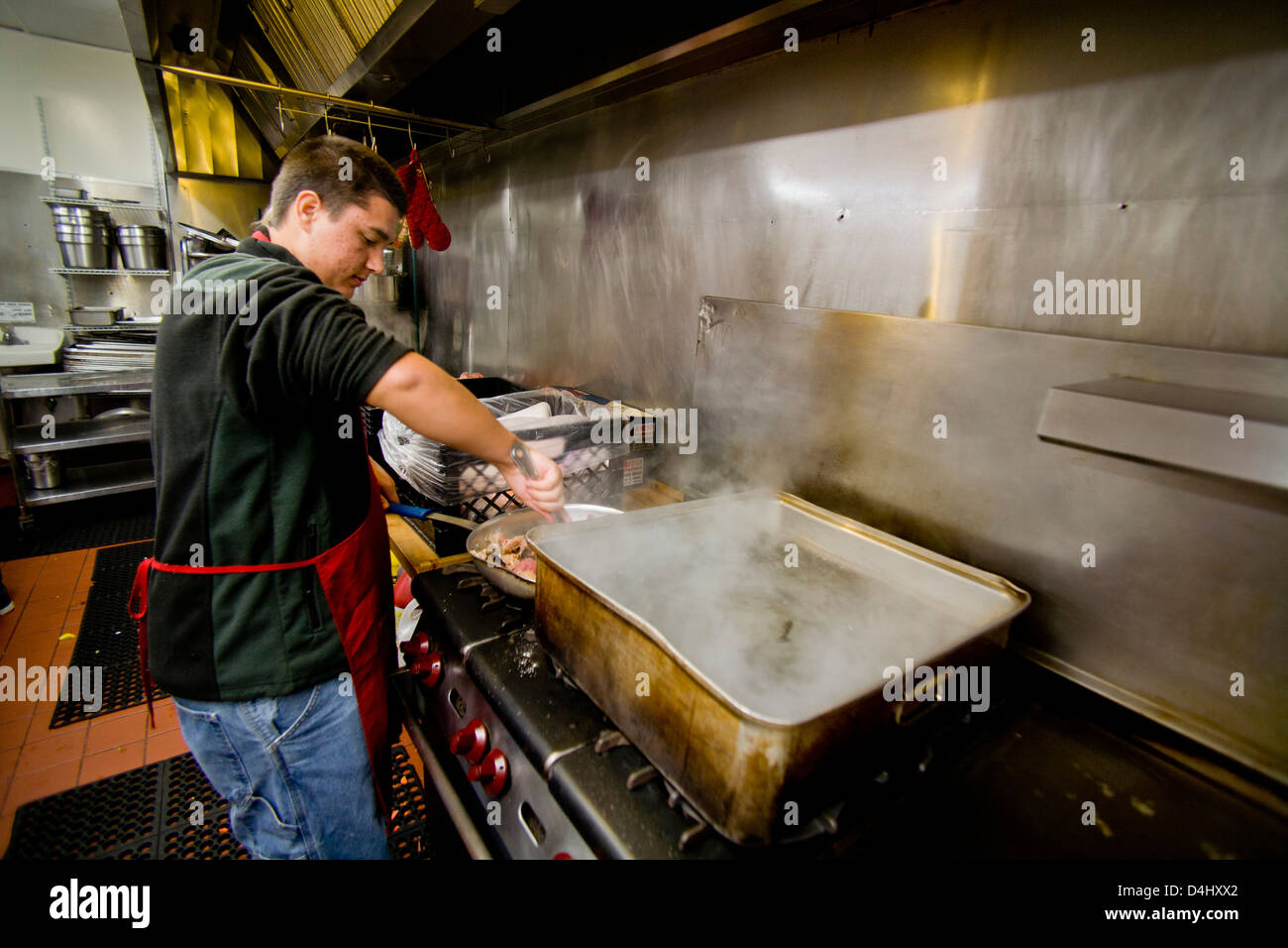 Middle class charitable volunteers pitch in at a Costa Mesa, CA, soup kitchen to feed the homeless. - Stock Image