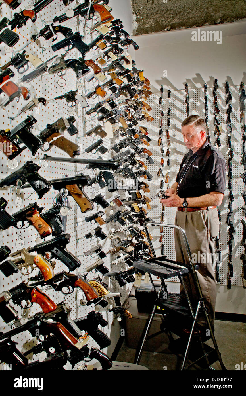 A forensics technician examines handguns used to commit crimes in Santa Ana, CA, stored in the police department - Stock Image