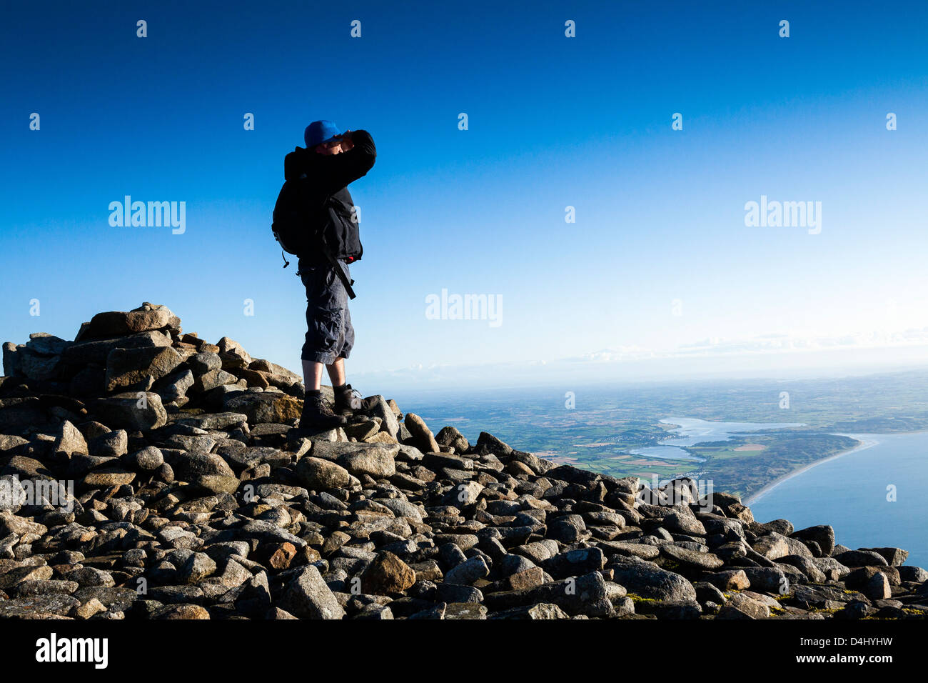 A mountaineer on top of a mountain. - Stock Image