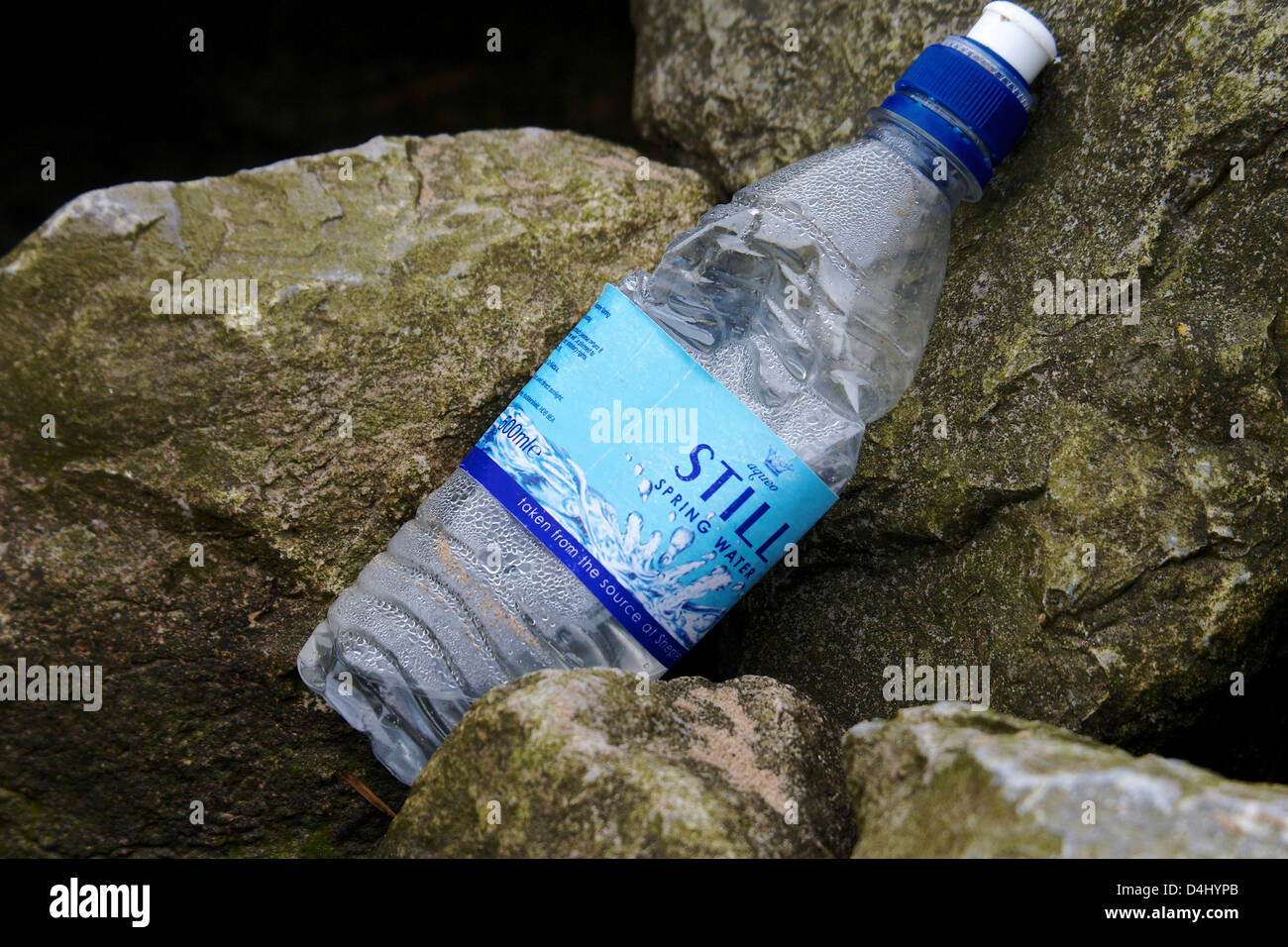 plastic bottle discarded on rocks at West Kirby Beach - Stock Image