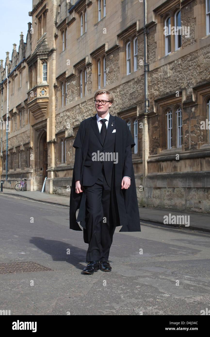 Man wearing academic dress outside Oriel College, University of Oxford, England, UK - Stock Image