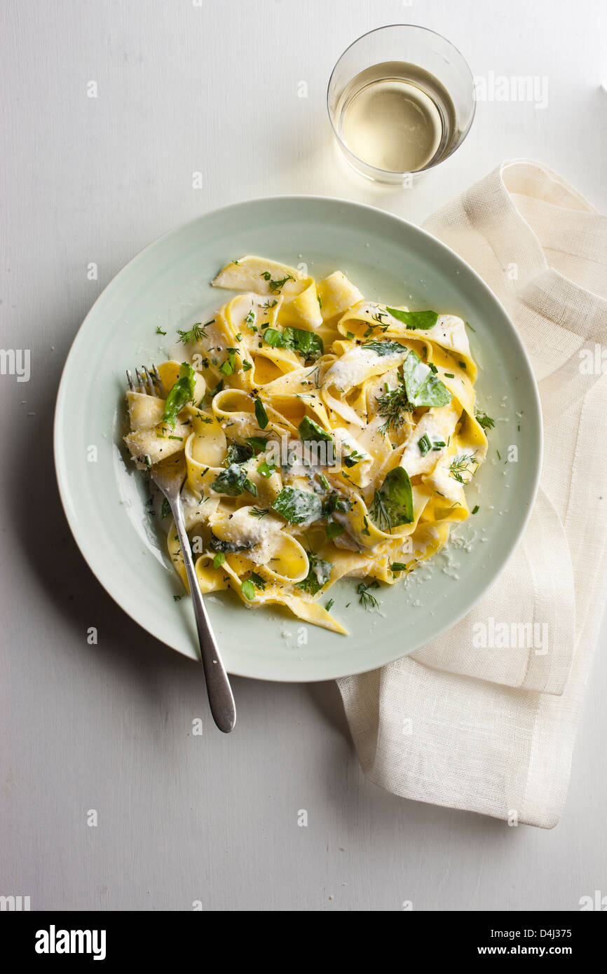 A plate of pappardelle pasta with creamy ricotta, baby spinach, fresh herbs and black pepper. - Stock Image