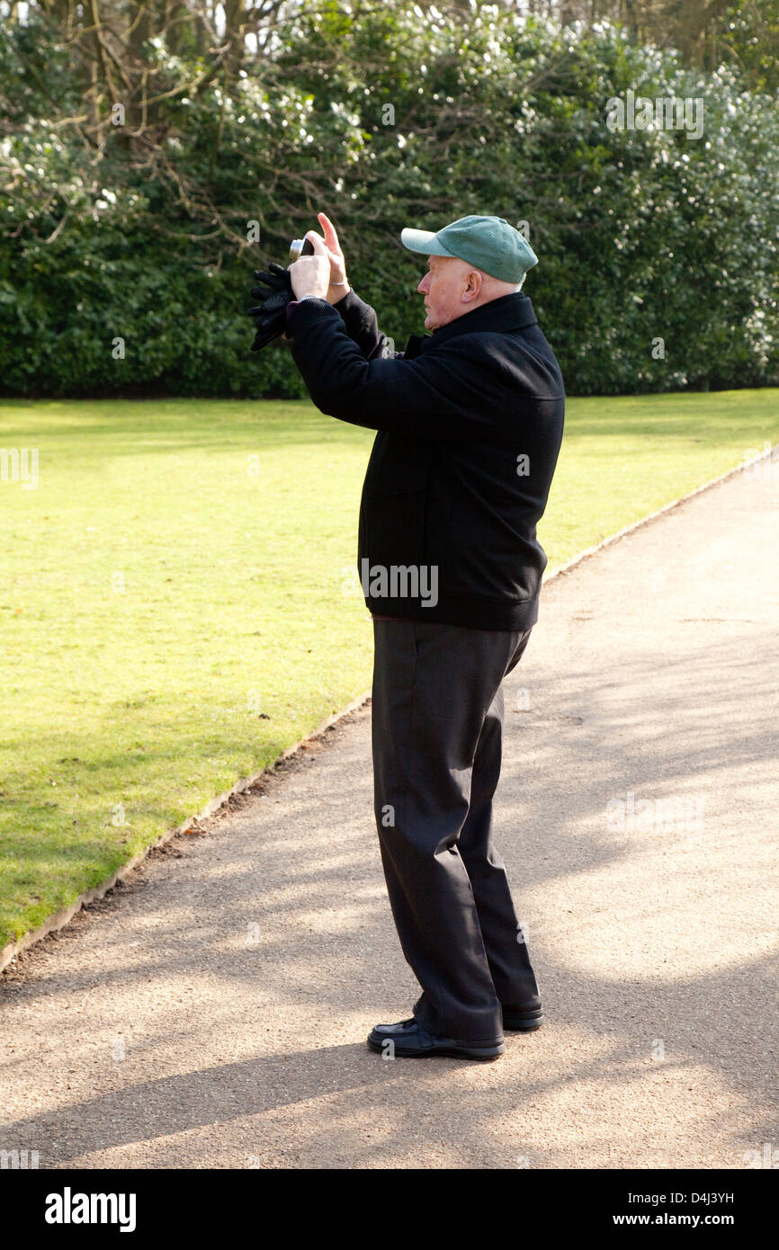 Elderly man taking a photo, photography as a hobby when retired, UK - Stock Image