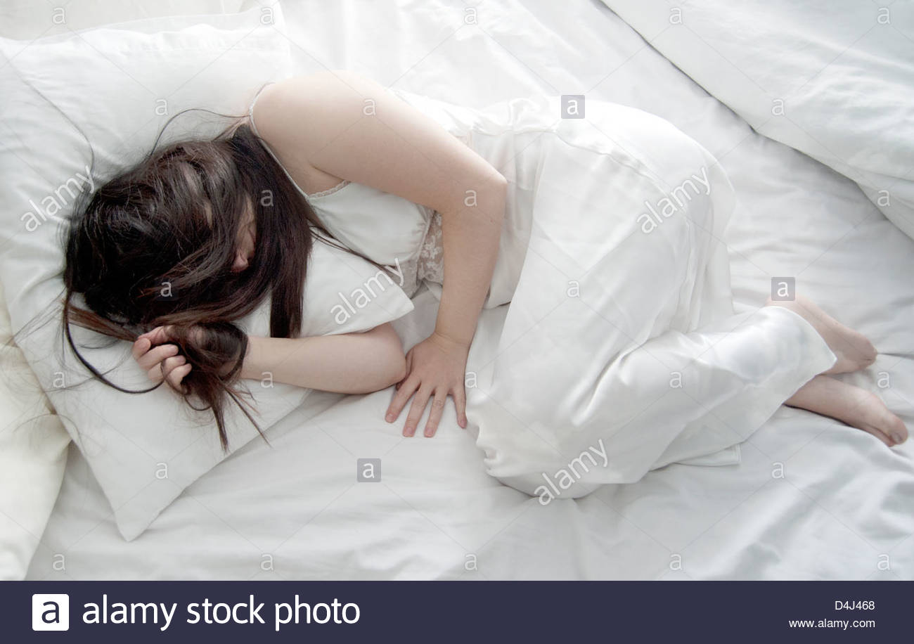 Full body view of woman with long hair sleeping in bed wearing white nightgown on white sheets - Stock Image