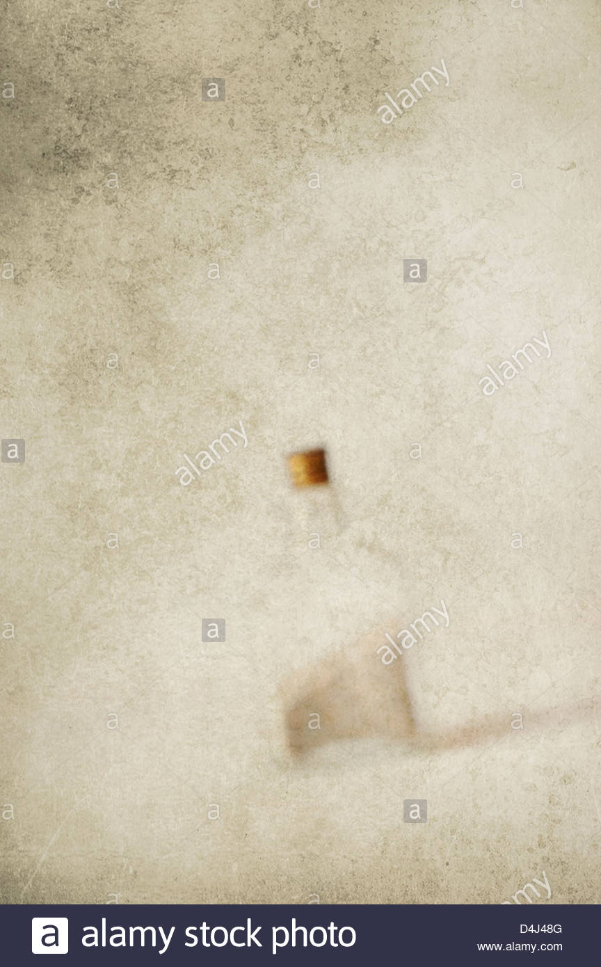 Blurred image of glass bottle filled with sand on textured background - Stock Image