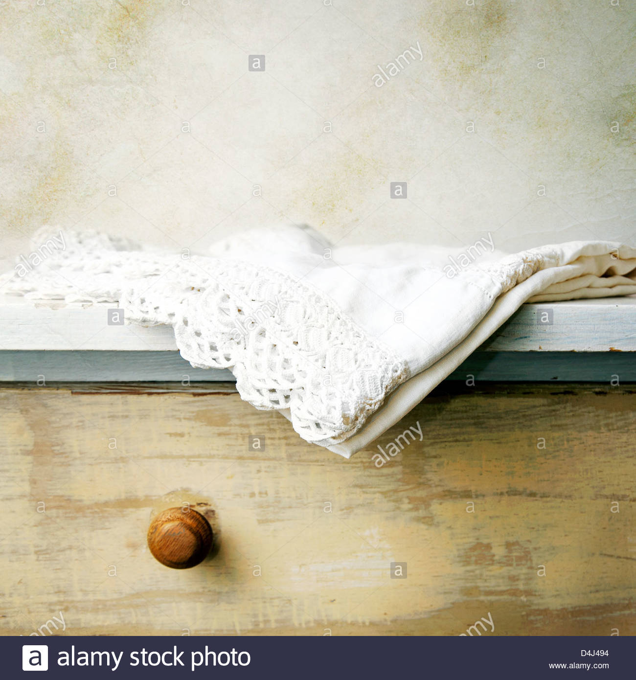 Old hand made lace pillow case hanging off edge of dresser in bedroom - Stock Image