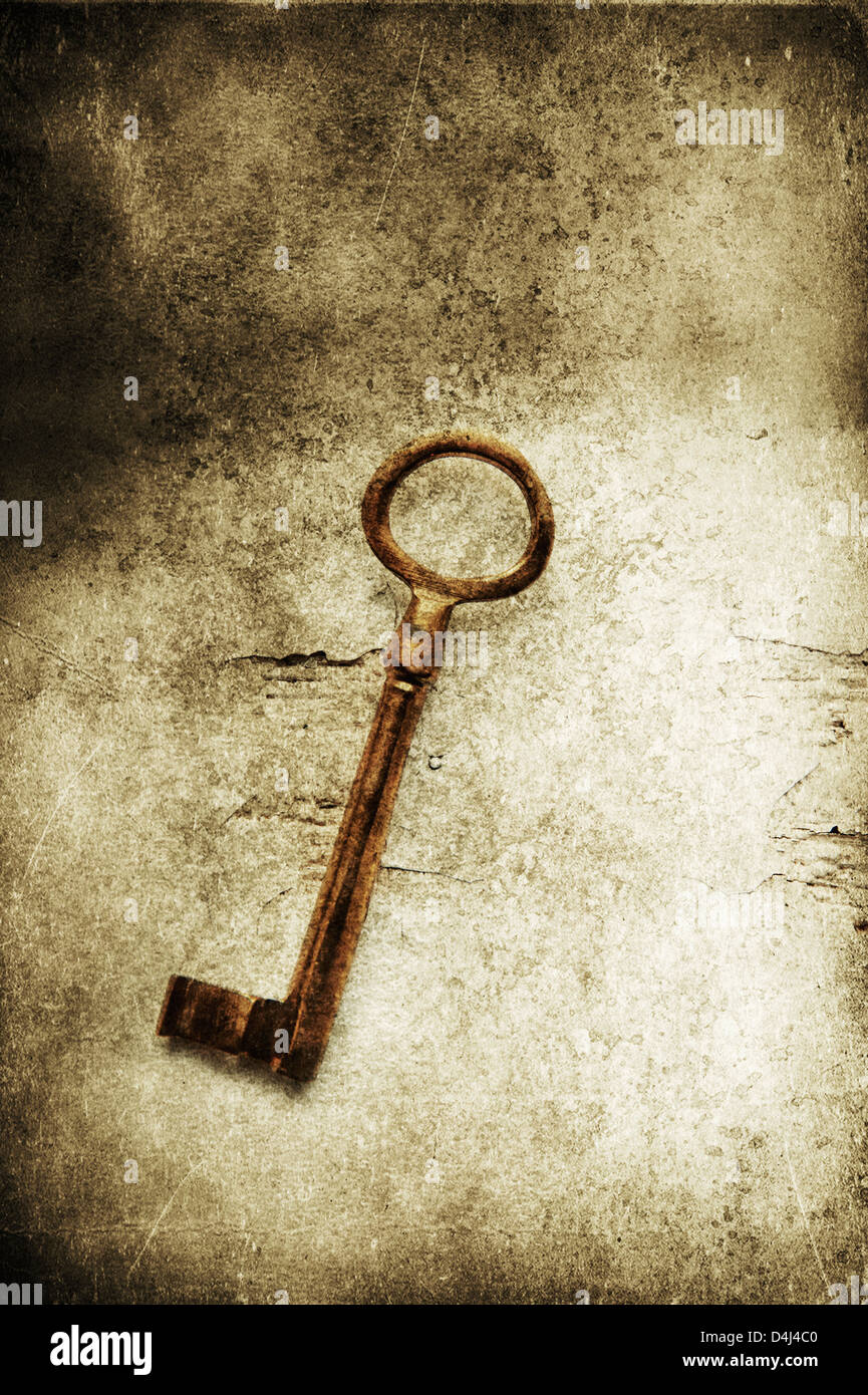 Old brass key on textured background - Stock Image