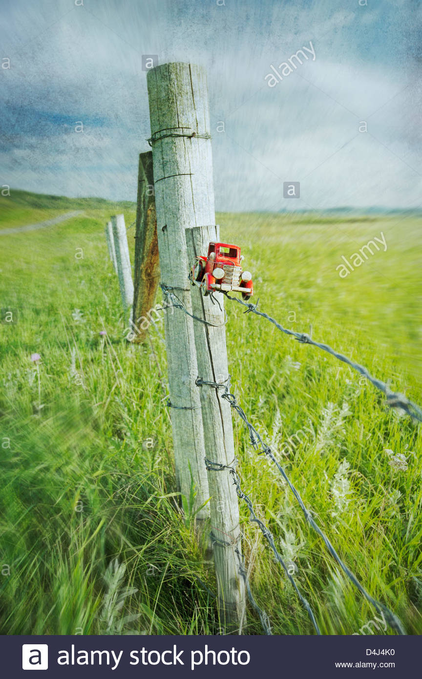 Red toy truck abandoned on a fence post with empty field and stormy skies beyond - Stock Image