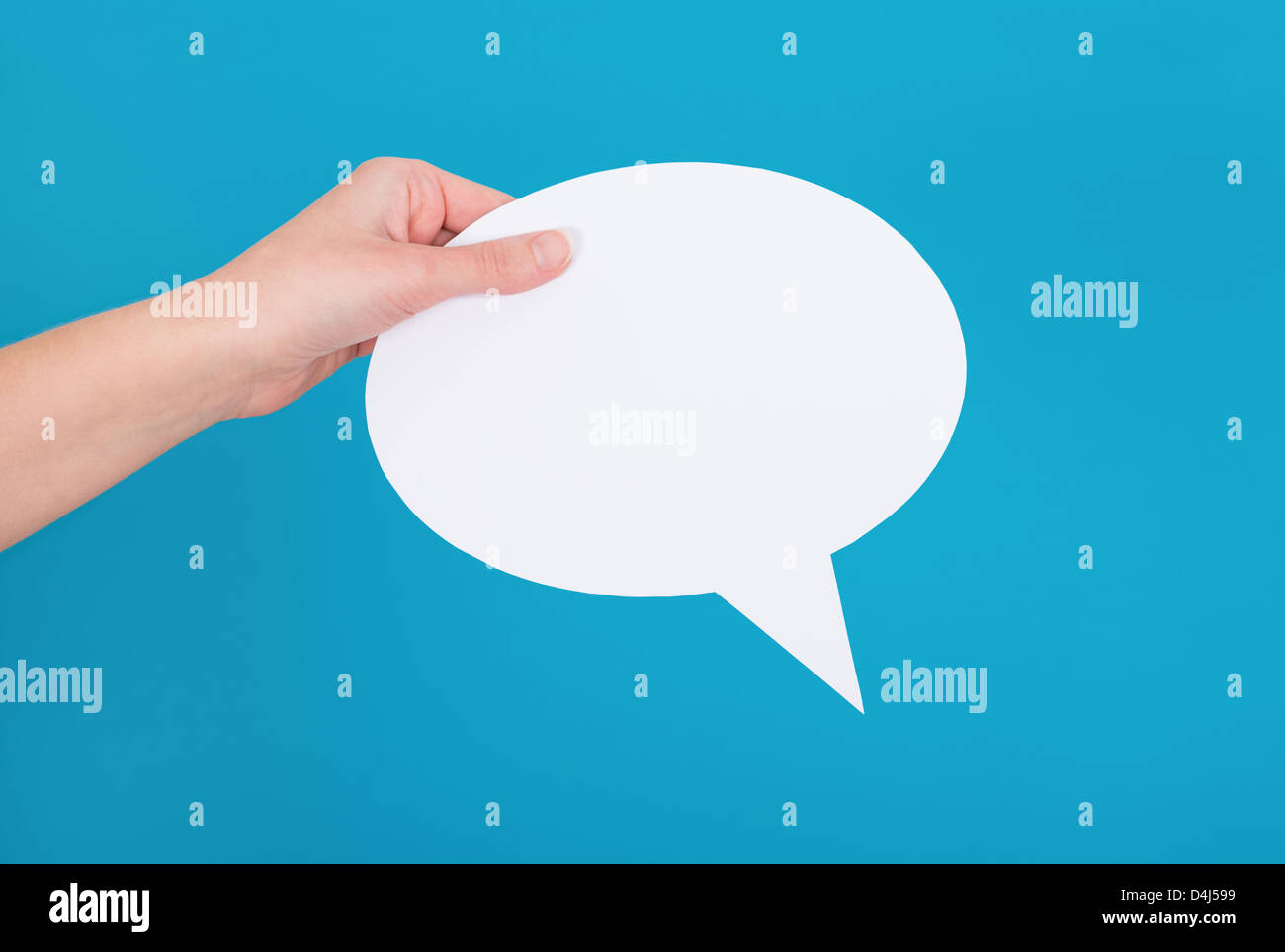Hand holding an empty speech bubble on blue background. - Stock Image