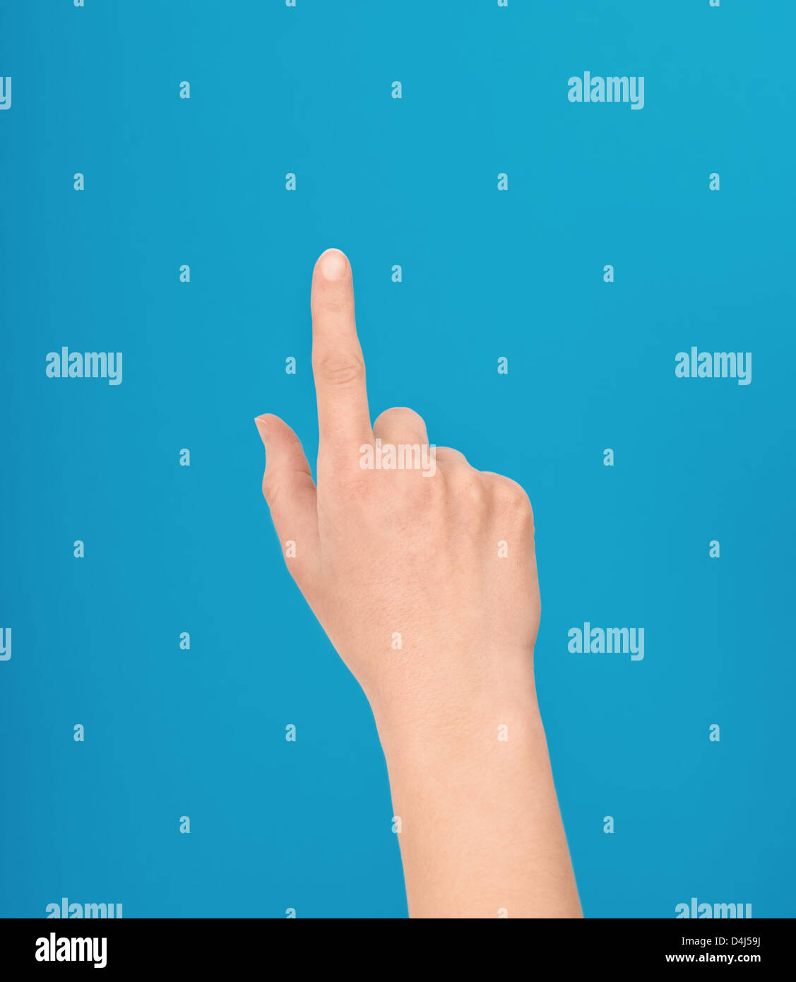 Hand making a touch gesture or touchscreen or a pointing with one finger isolated against a blue background - Stock Image