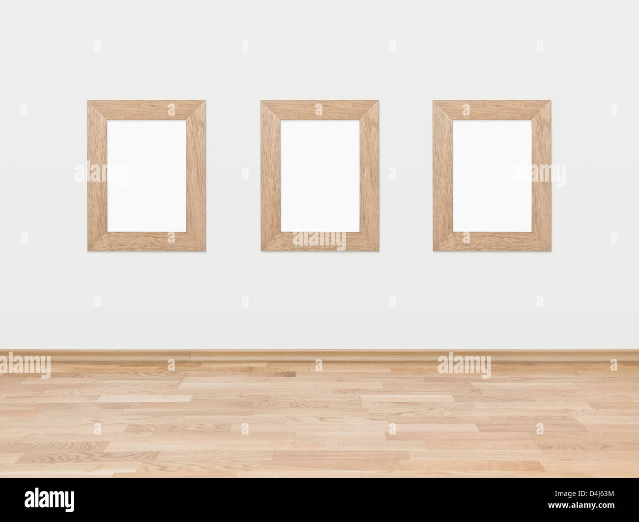 Three empty rectangular wooden frames displayed on a white wall above a hardwood wooden floor. - Stock Image