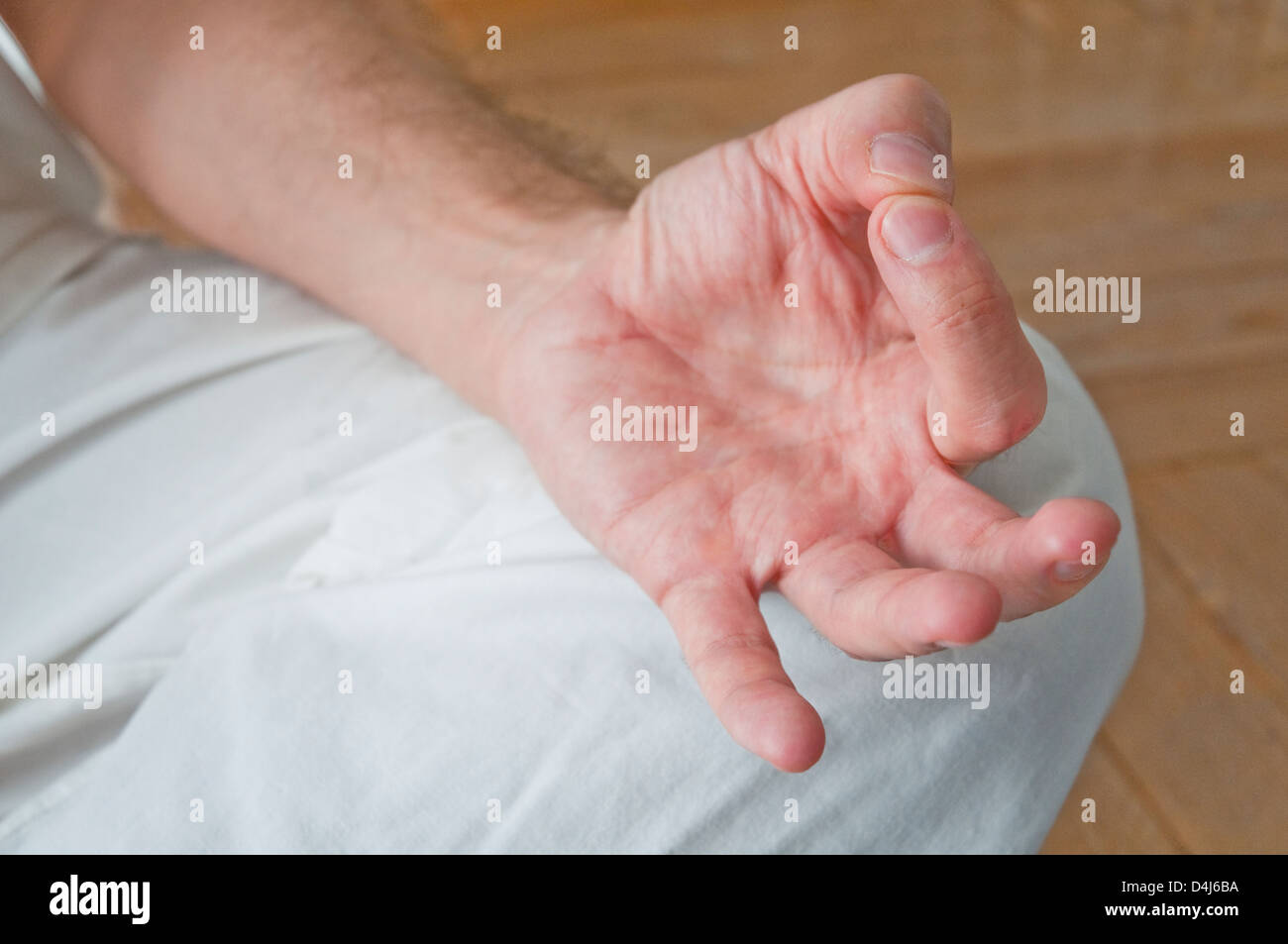 Man practicing yoga, sitting in the lotus position. Detail of his hand. - Stock Image