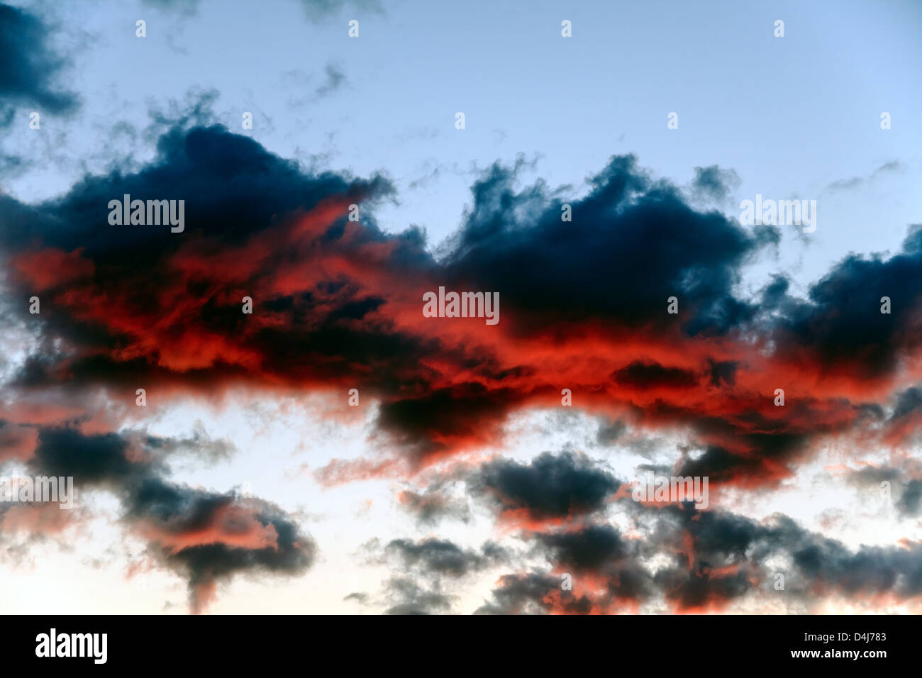 Dark clouds illuminated by a strong red light of the setting sun - Stock Image