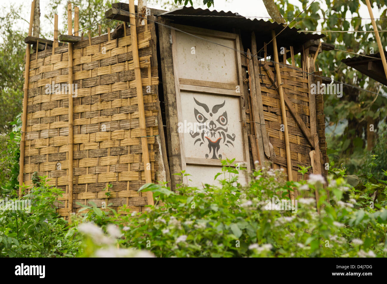 A fierce mask face painted on a bamboo shed - Stock Image