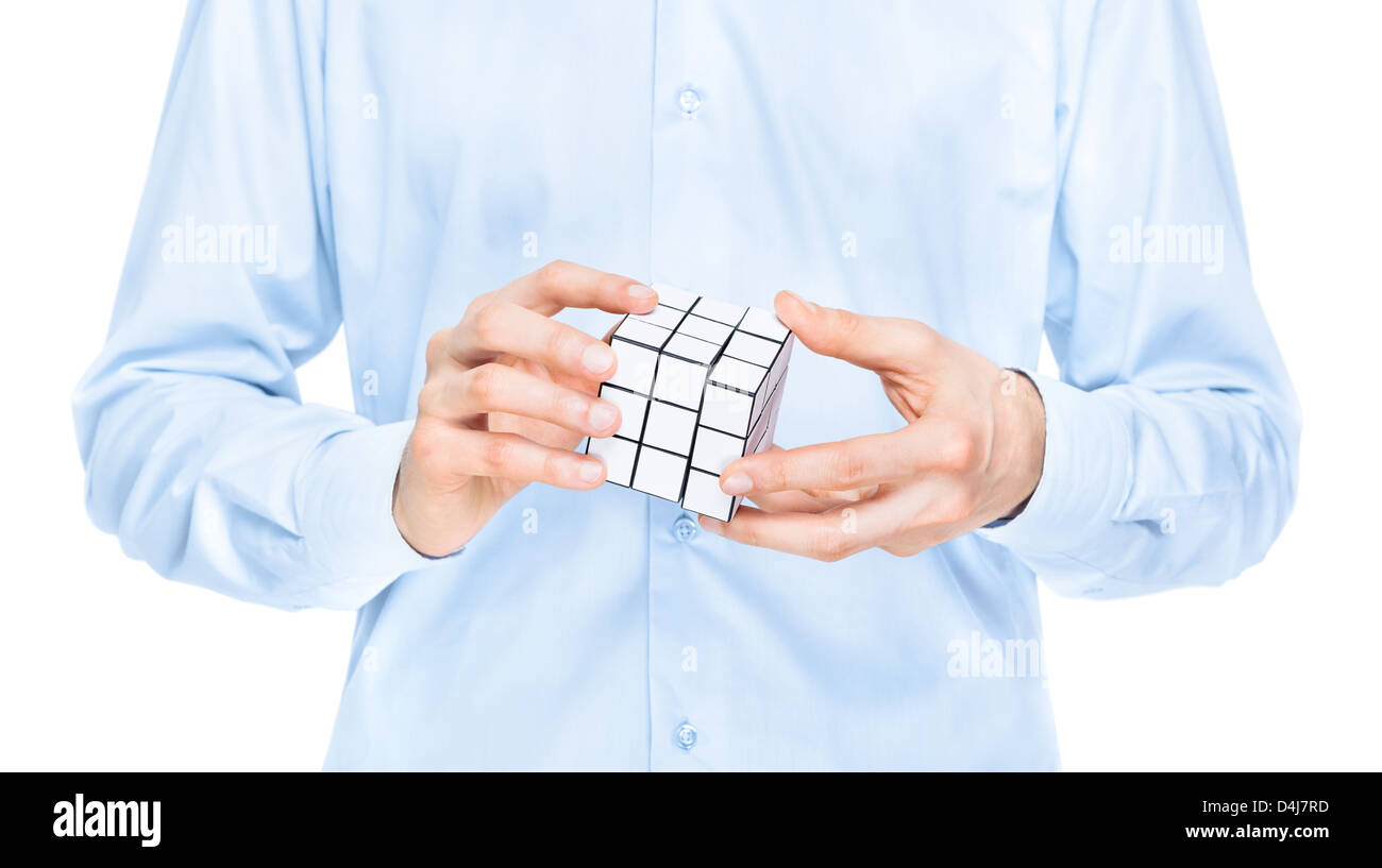 Cropped view of the torso and hands of a man holding a blank white cubic twist puzzle game which he is trying to - Stock Image