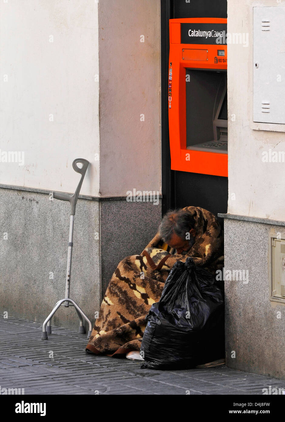 homeless Man wrapped in a blanket sits in front of an automatic cashier of the spanish bank 'CatalunyaCaixa' - Stock Image