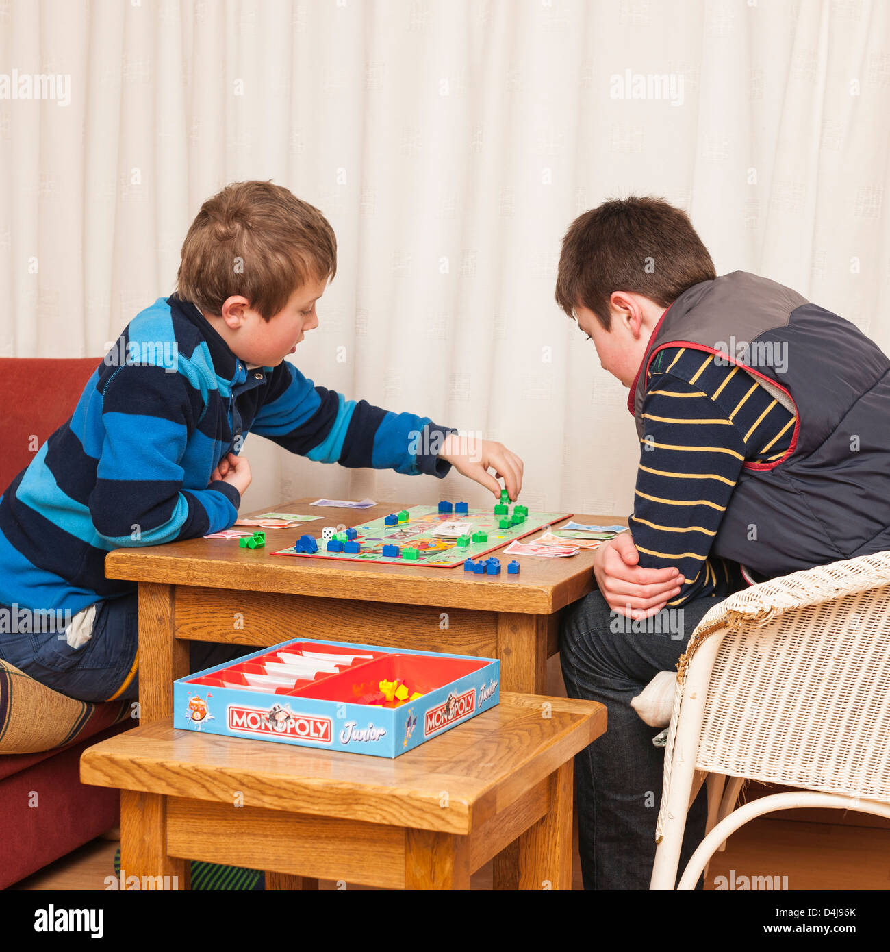 Two boys ( brothers ) playing junior monopoly board game at home - Stock Image