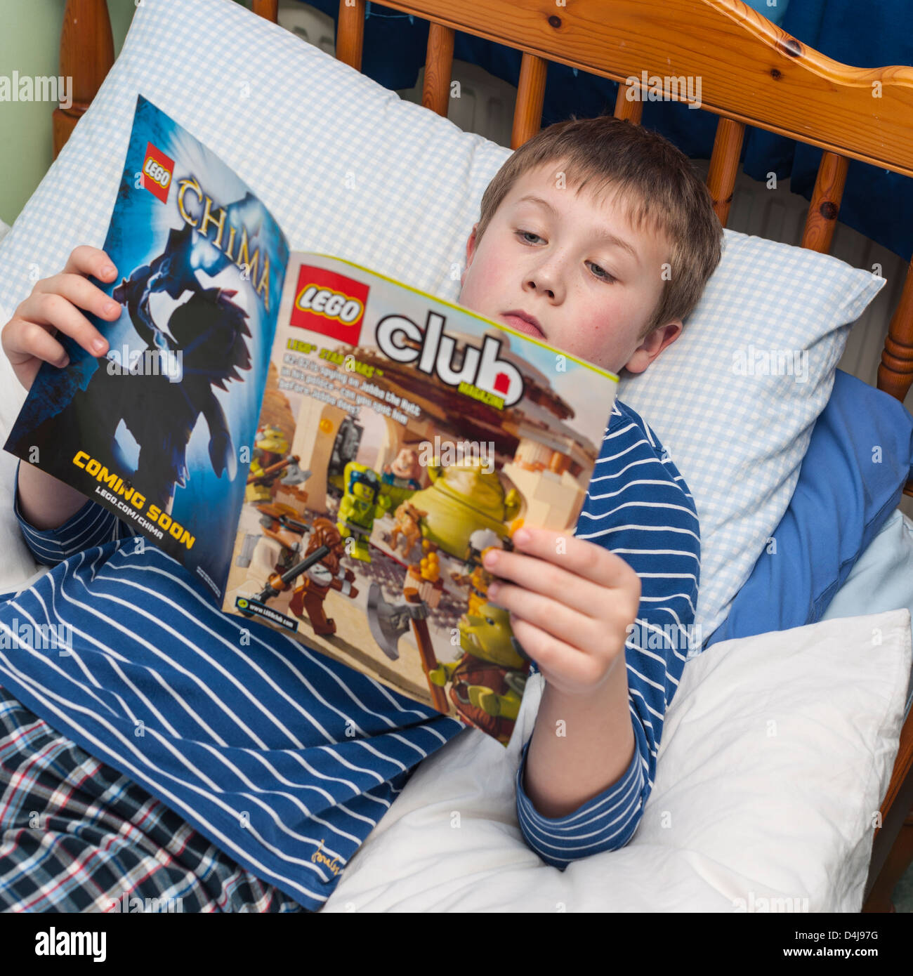 A nine year old boy reading the Lego club magazine in his bedroom - Stock Image