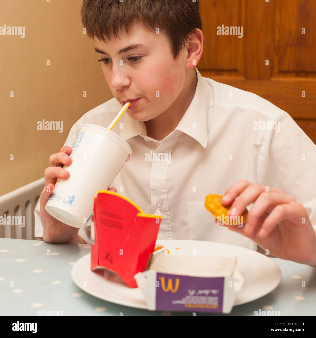 A thirteen year old boy eating a Mcdonalds meal at home in the Uk - Stock Image