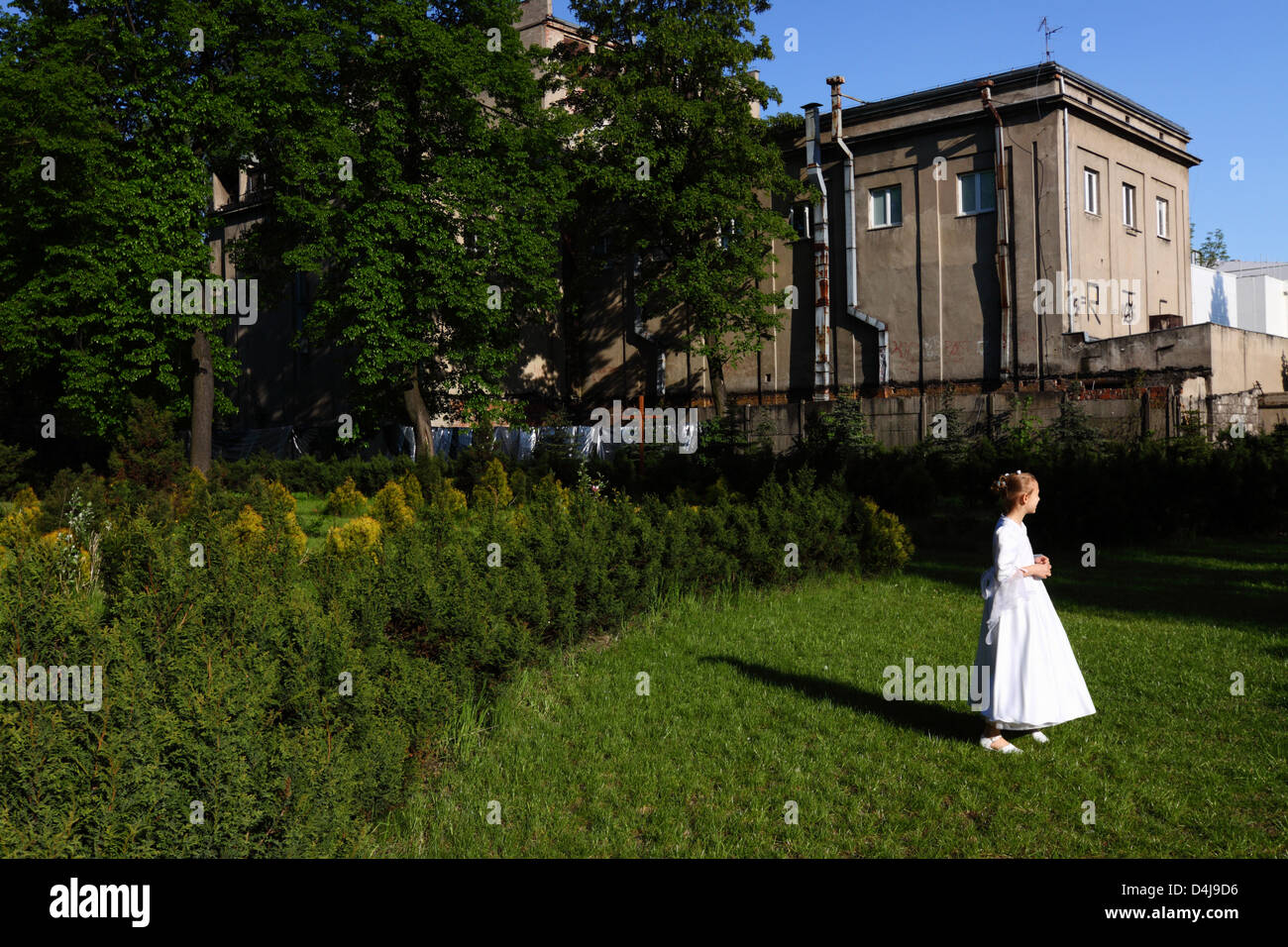 Girl in her First Communion dress in the backyard garden of an old church in Lodz, Poland - Stock Image