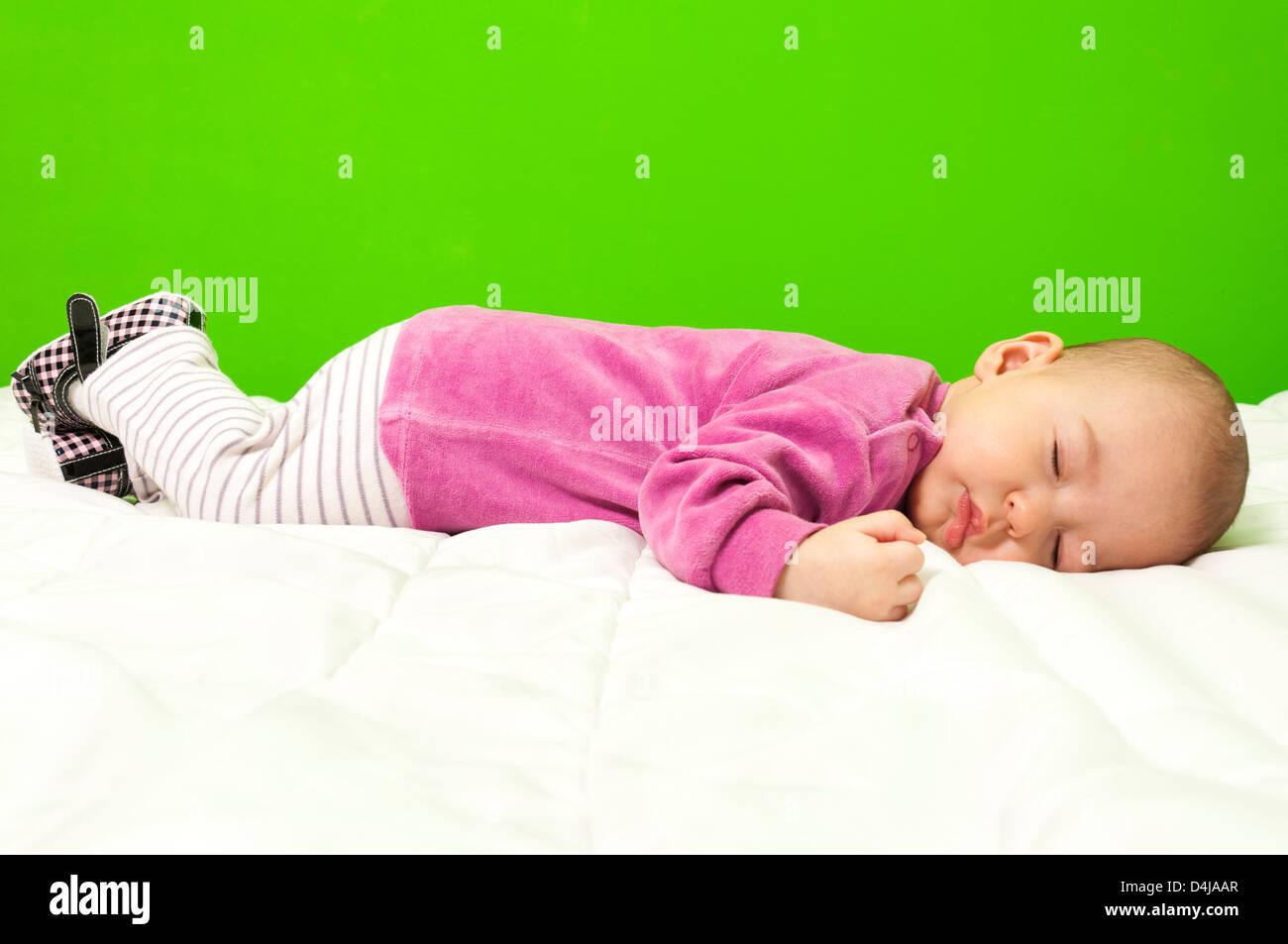 Sleeping baby girl on the white blanket - Stock Image