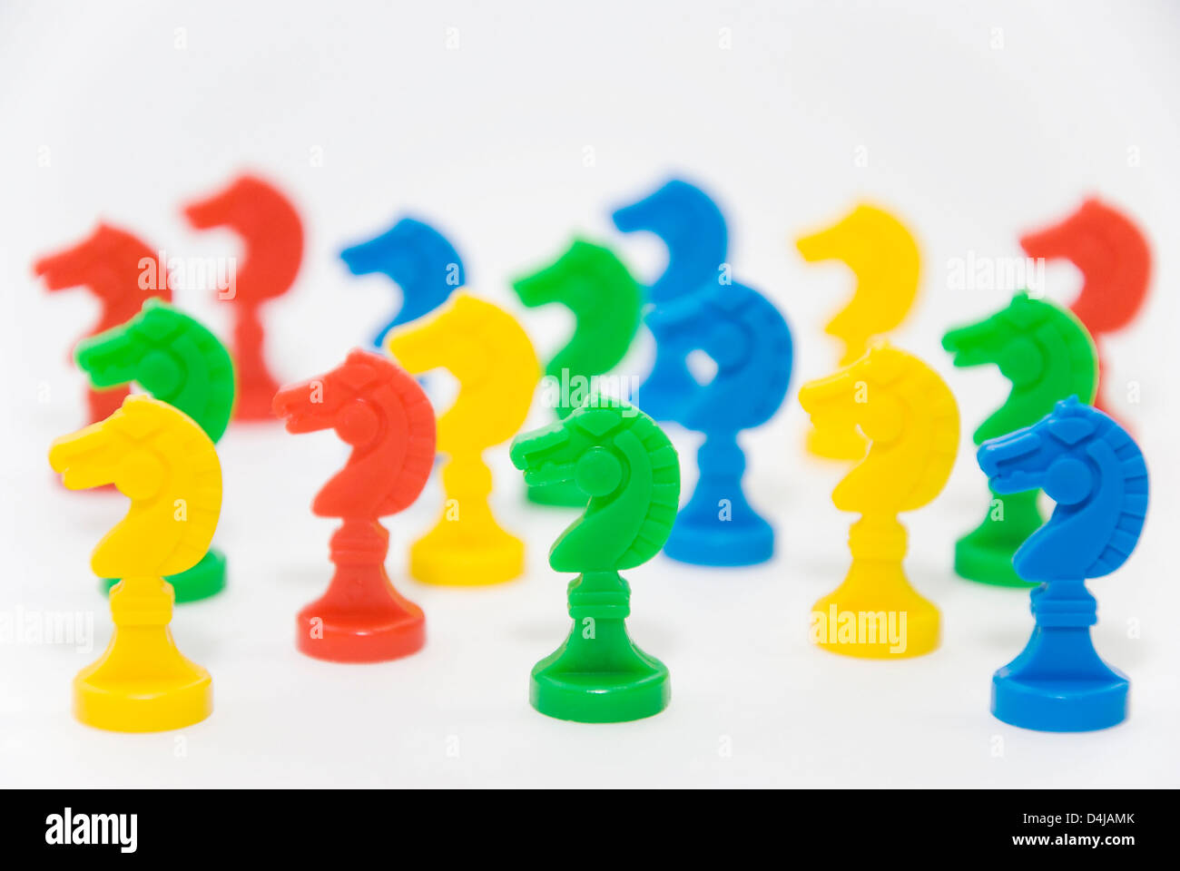 chess chips colored horses on white background - Stock Image