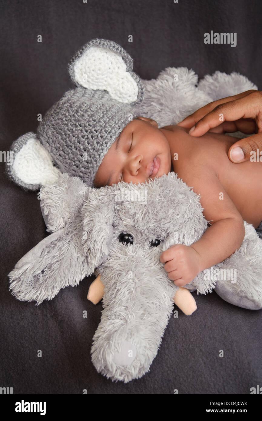 A Newborn Baby Boy Wearing A Crocheted Elephant Hat And Sleeping On