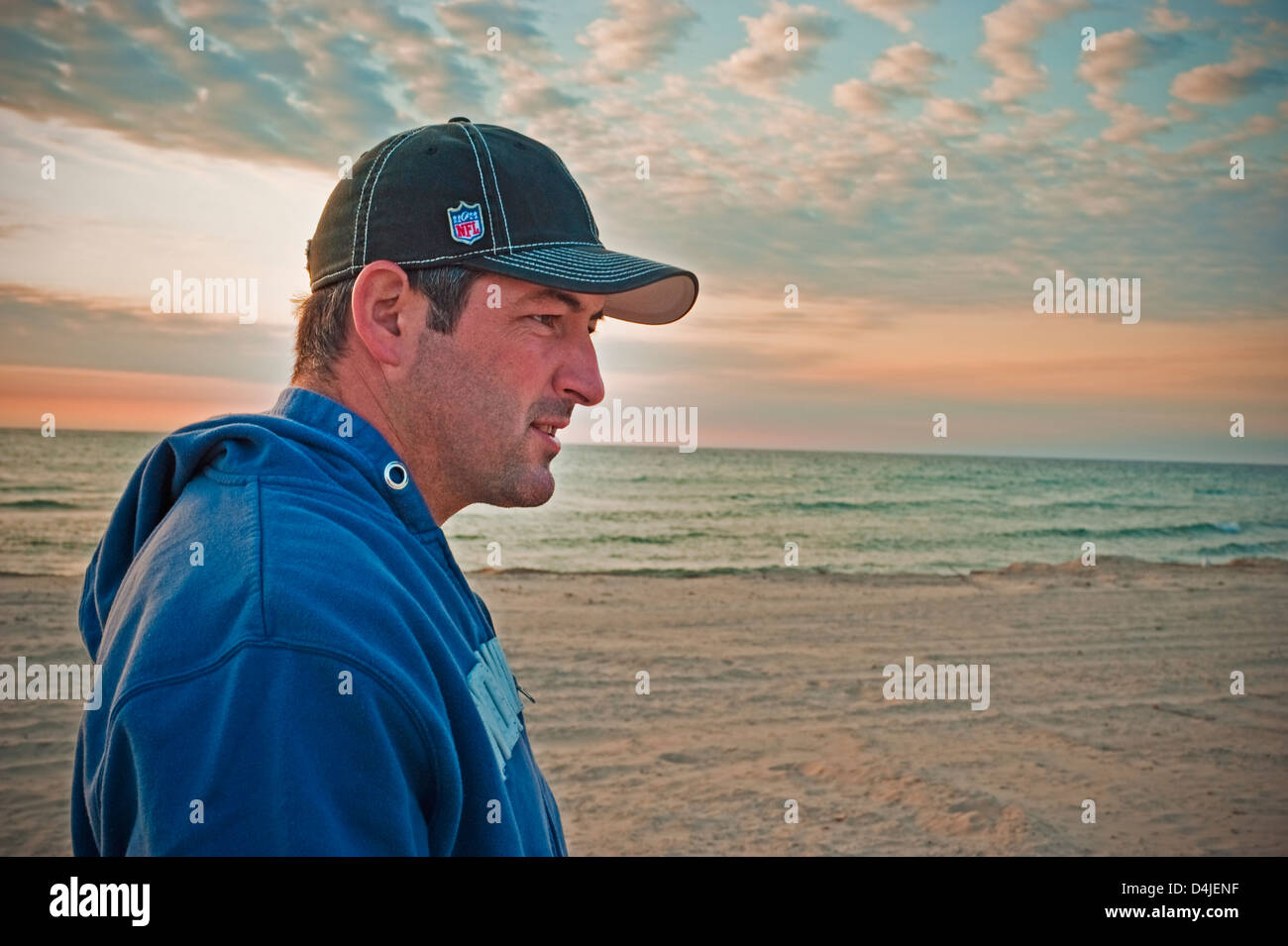 03d819745fe Man wear baseball cap and sweat shirt enjoying an autumn evening on a Lake  Michigan beach near Ludington