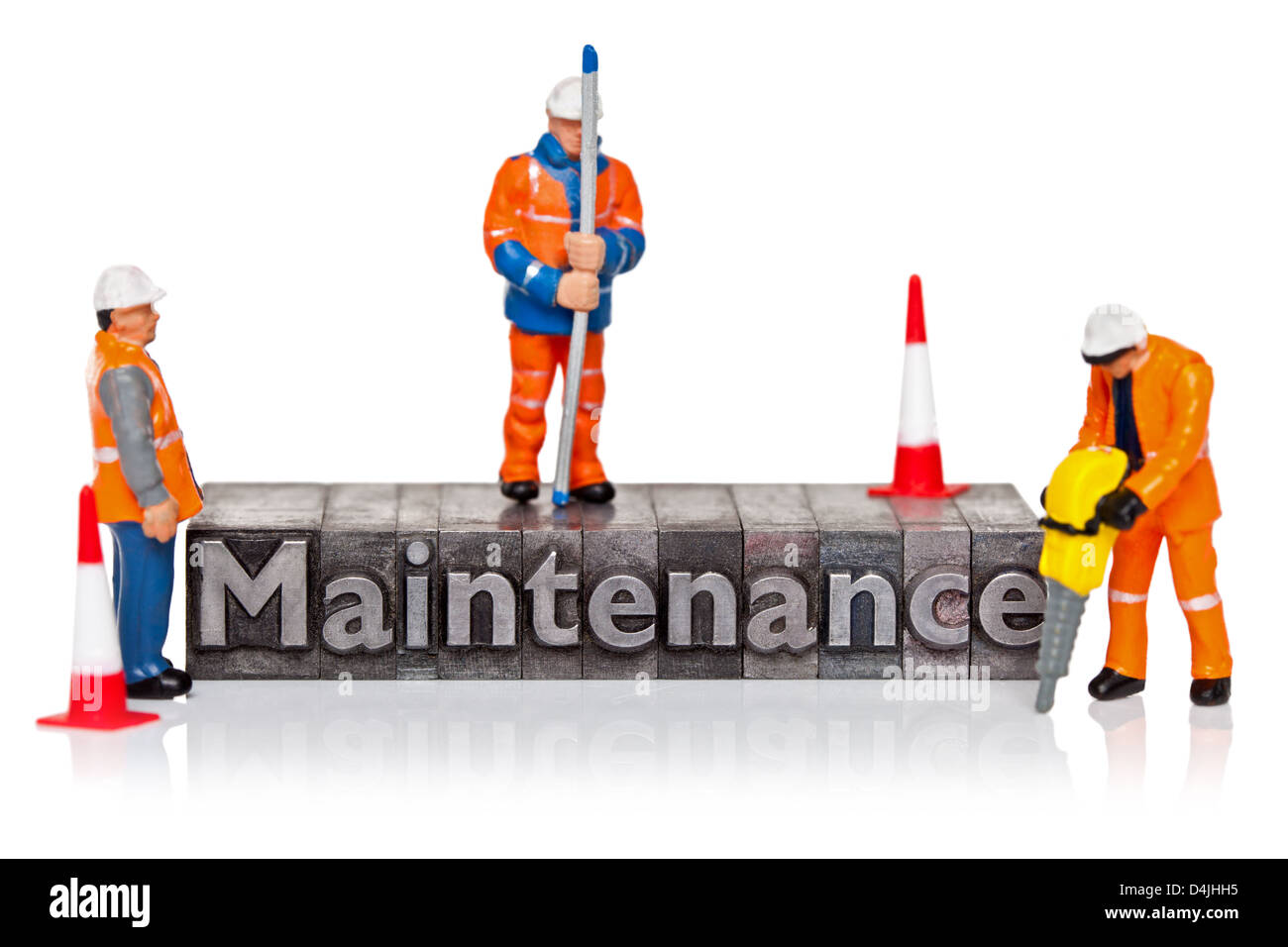 Hand painted miniature workmen figurines and the word Maintenance in old metal letterpress isolated on a white background. - Stock Image