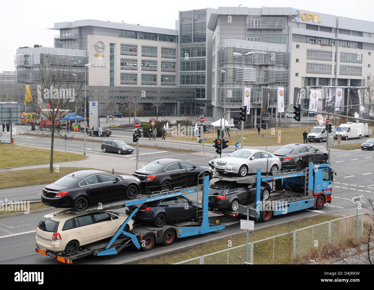 A car transporter with new Opel cars drives past the Opel