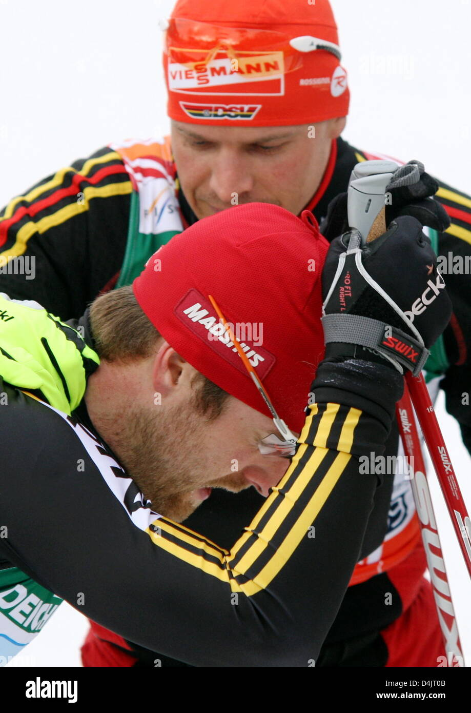 Germany?s Axel Teichmann (front) is consoled by his team-mate Tobias Angerer (back) after the men?s cross-country - Stock Image