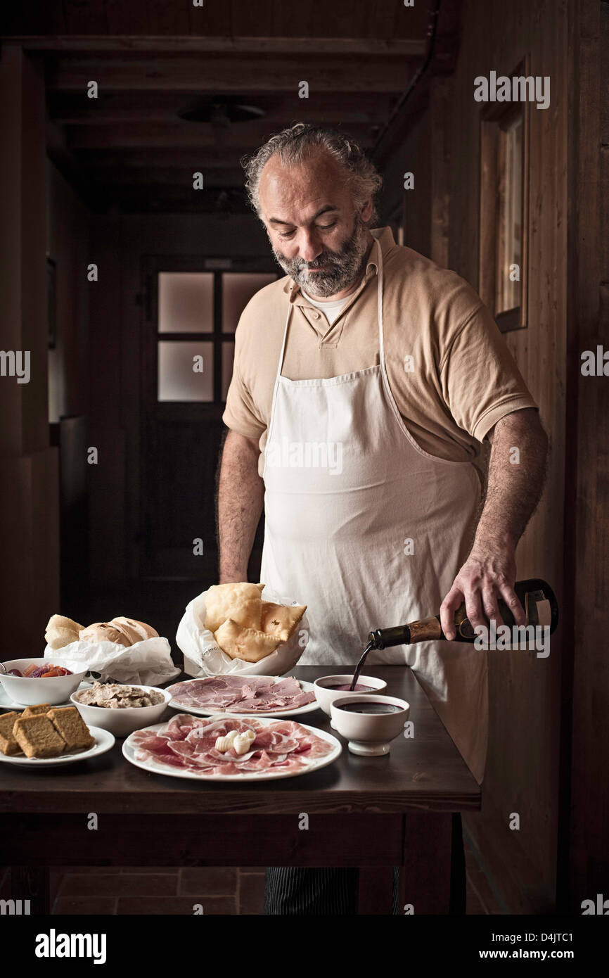 Man laying out meat, bread and sauce - Stock Image