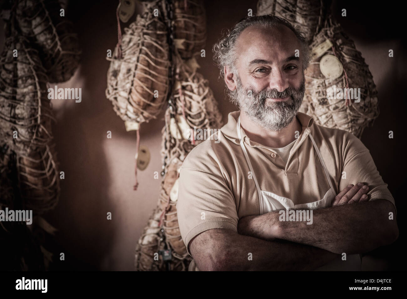 Butcher standing by hanging meat - Stock Image