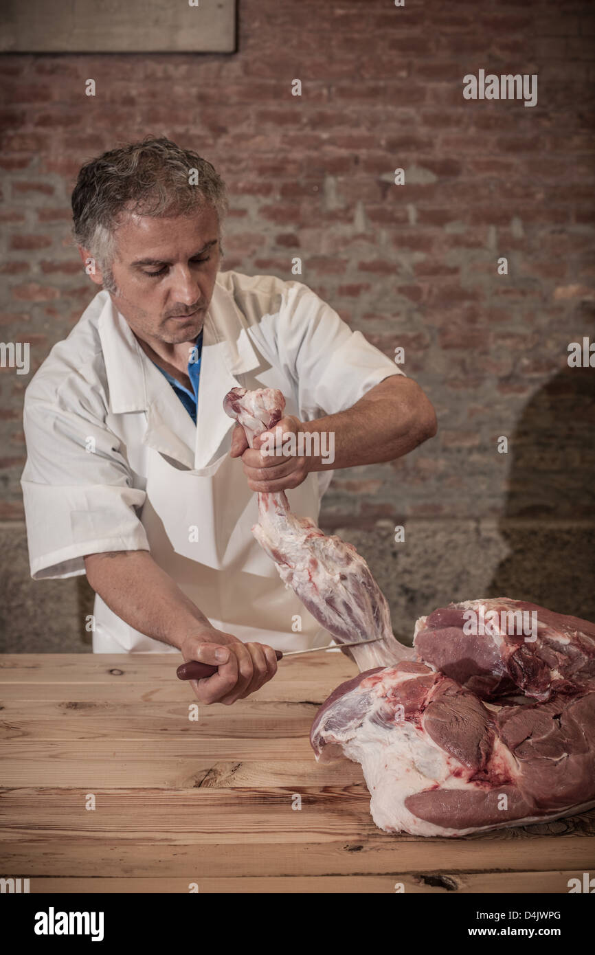Butcher carving meat in shop - Stock Image
