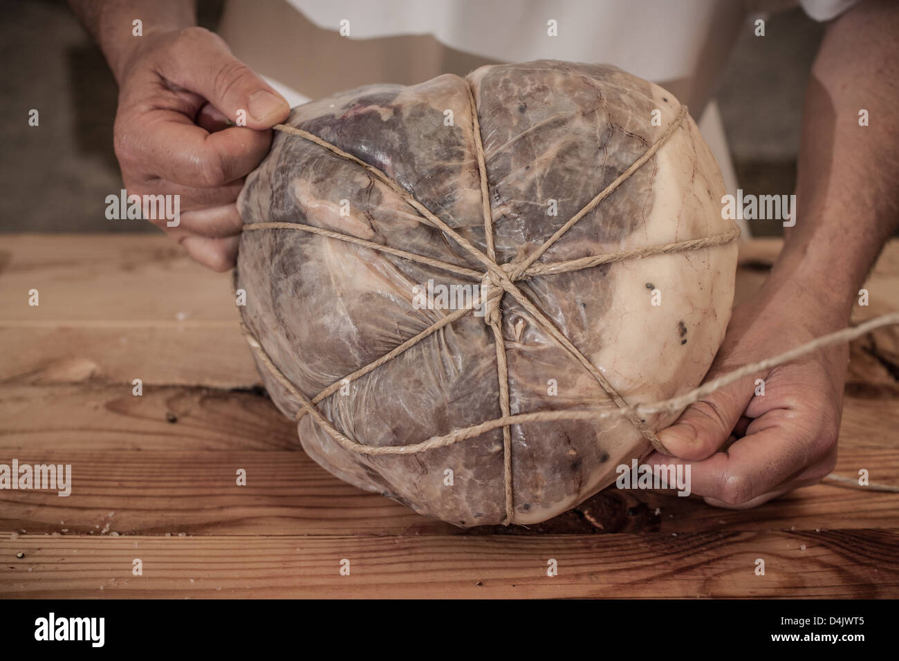 Butcher tying meat in shop - Stock Image