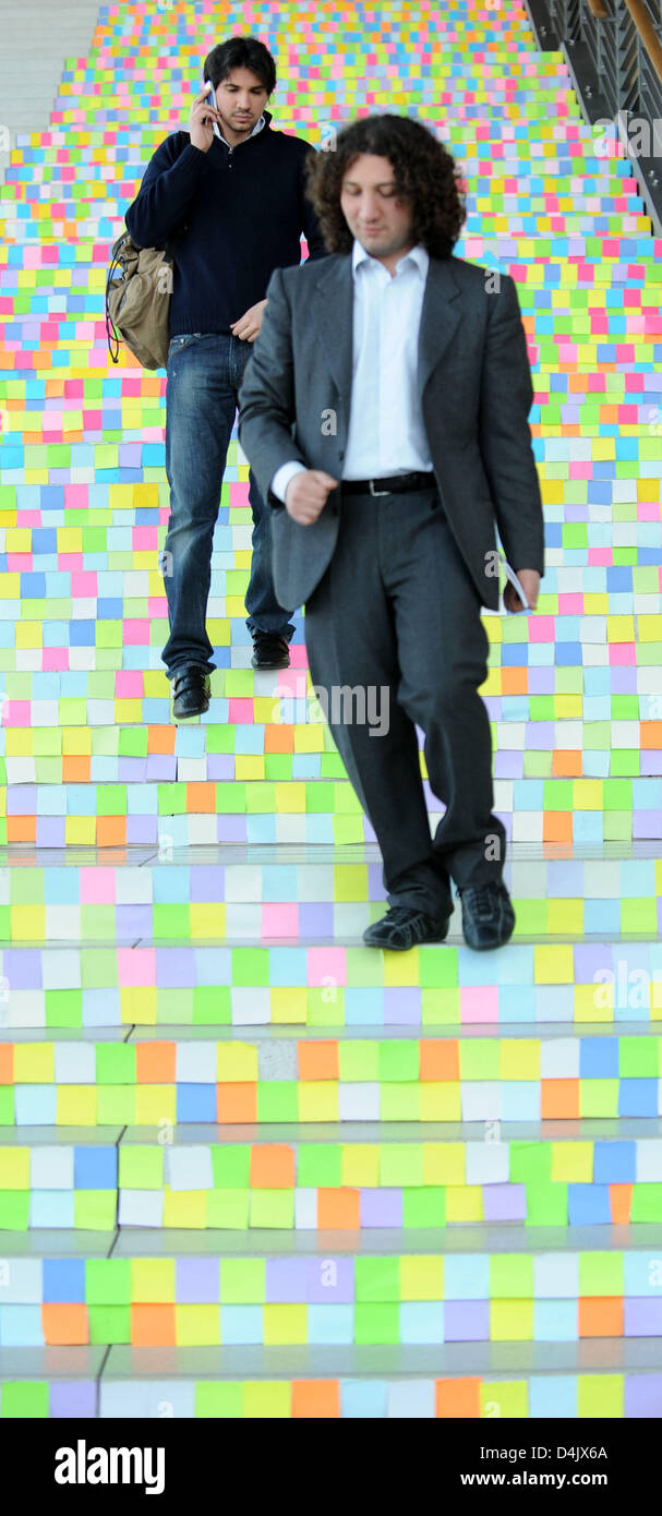 Visitors walk down stairs which are pasted up with thousands of ?Haftis? at the trade fair ?CeBIT? in Hanover, Germany, - Stock Image
