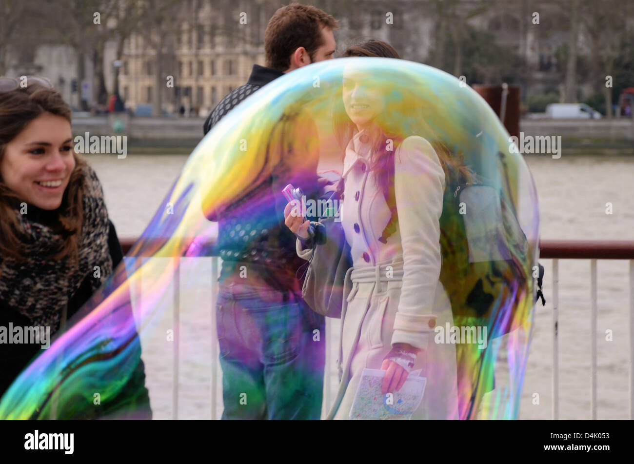 A large bubble creates effects around female walking by whilst another girl looks on happily - Stock Image