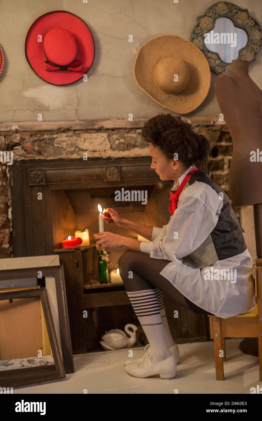 Woman lighting candles in fireplace - Stock Image