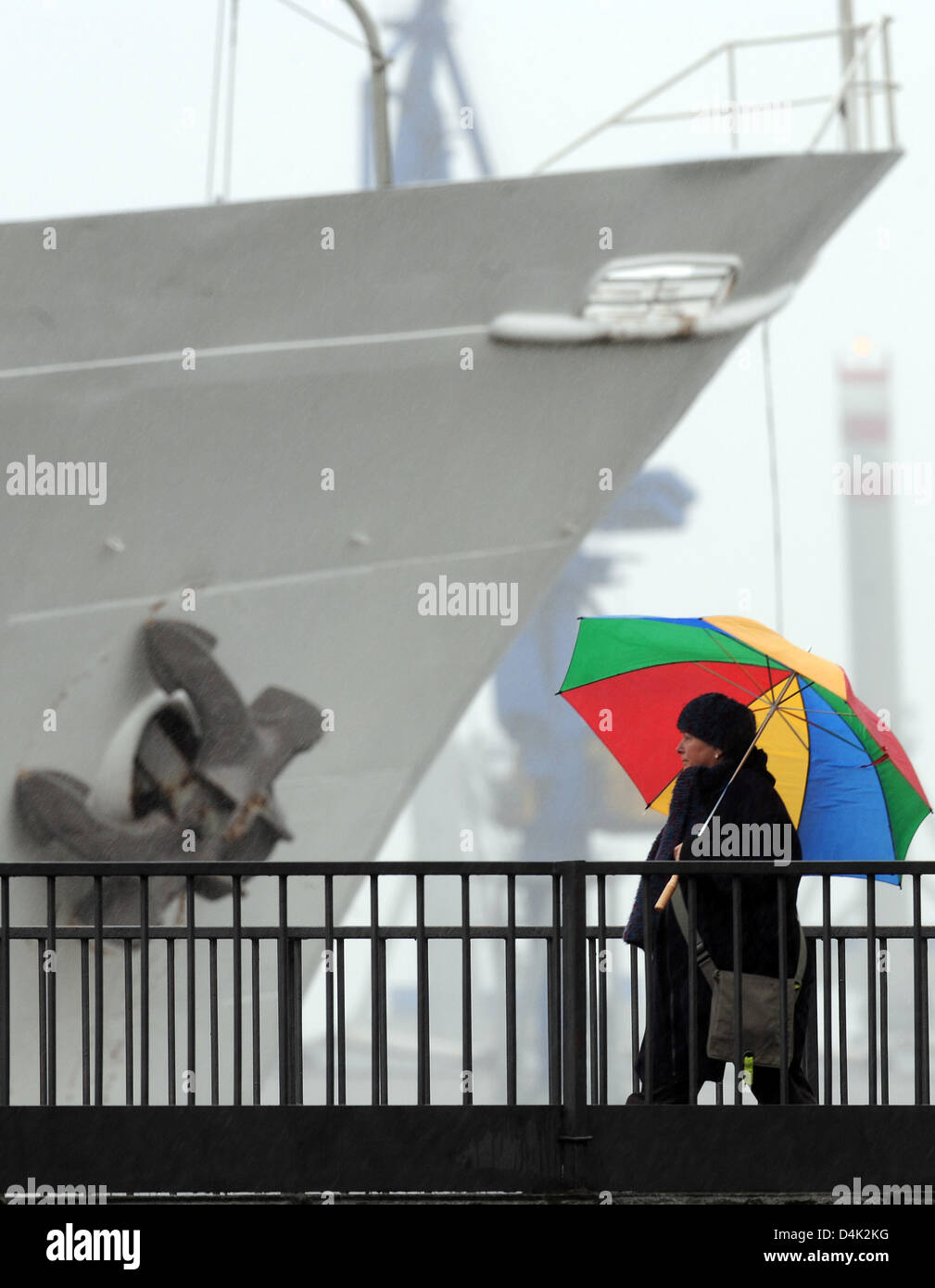 A woman walks past a grey ship with her colourful umbrella in the pouring rain near the waterfront at Hamburg?s - Stock Image