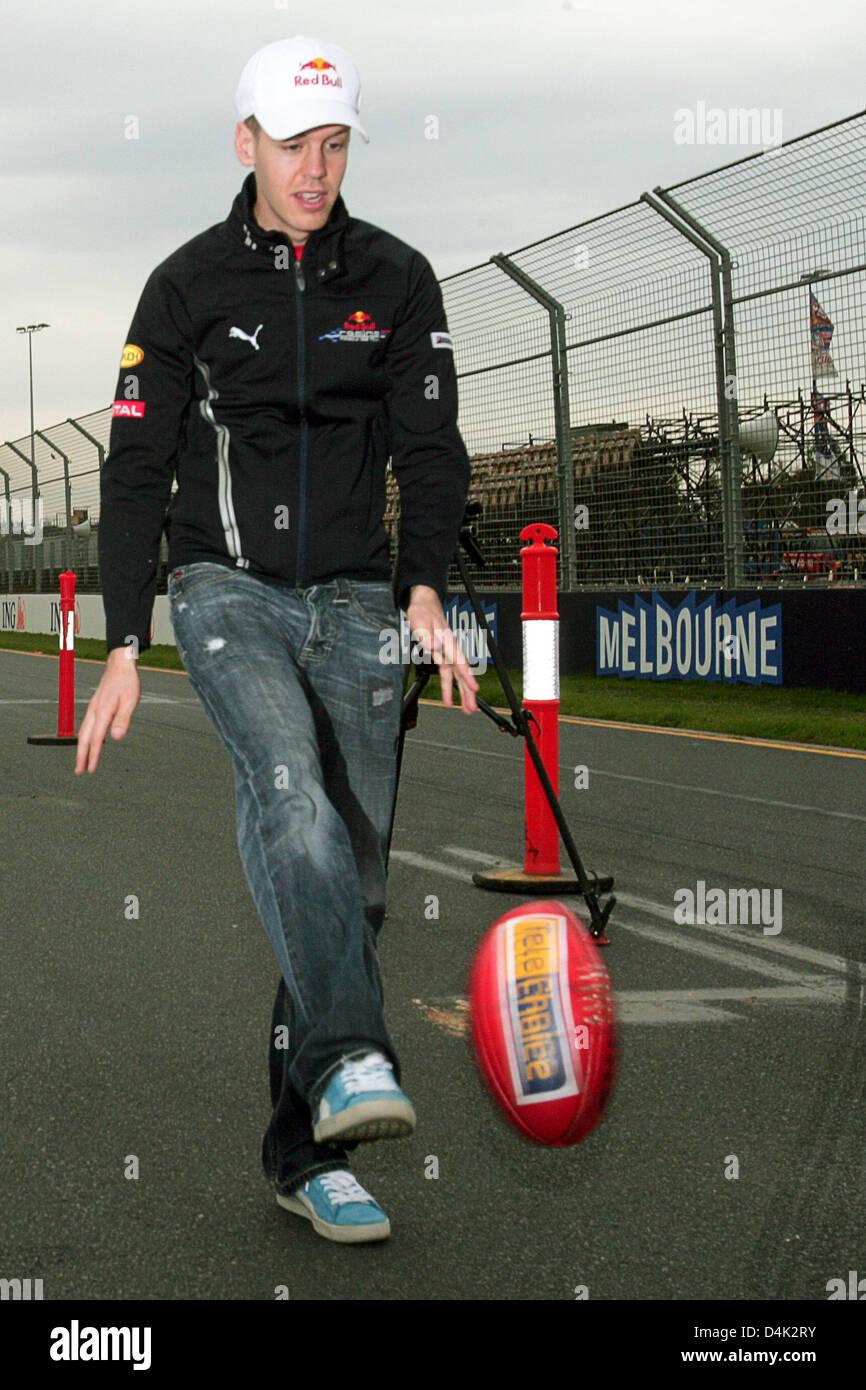German Formula One driver Sebastian Vettel of Red Bull Racing-Renault kicks a footie at Albert Park street circuit - Stock Image