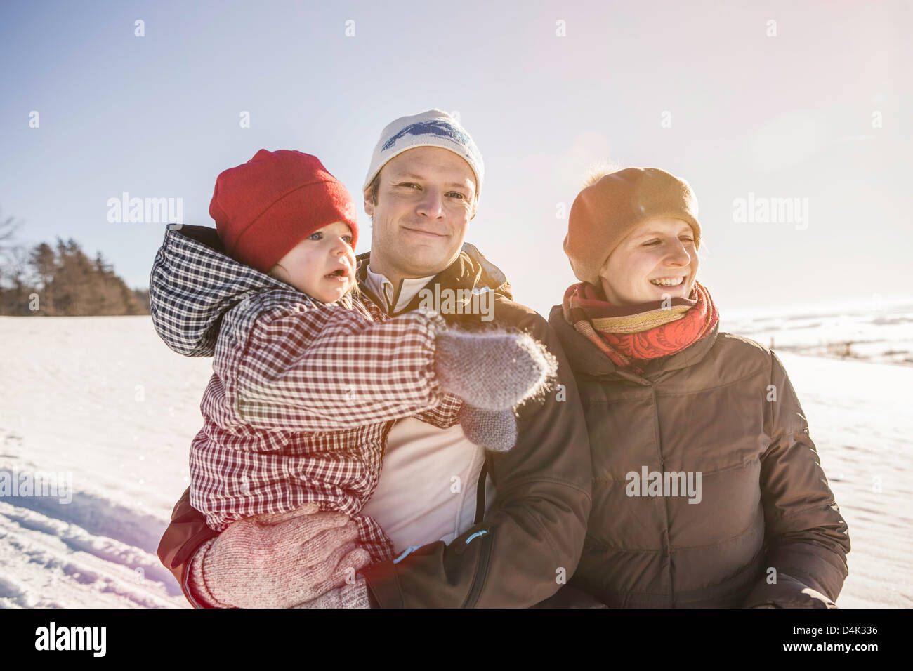 Smiling family walking in snow - Stock Image