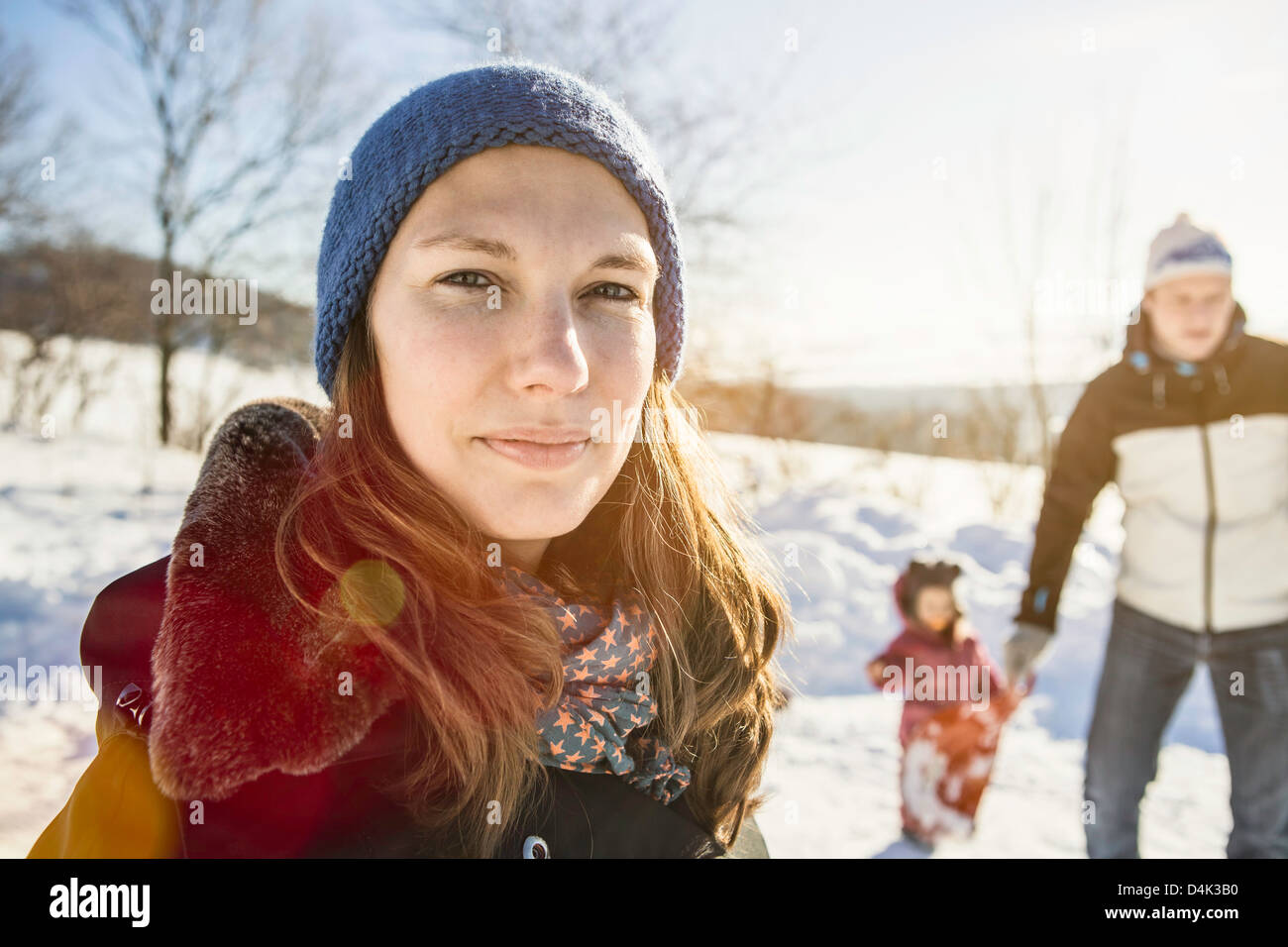 Woman walking with family in snow - Stock Image