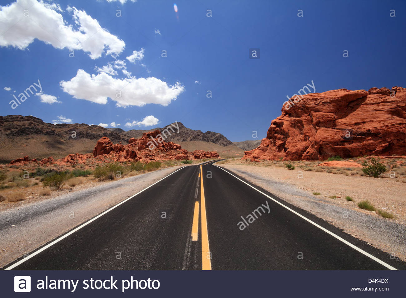 Rural road and red rock formations - Stock Image