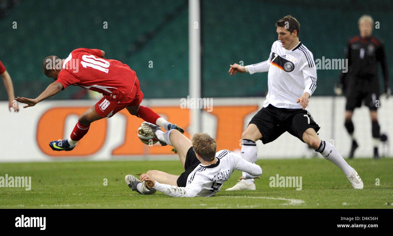 Germany?s Per Mertesacker (C) and Bastian Schweinsteiger (R) vie for the ball with Wales? Robert Earshaw (L) during Stock Photo