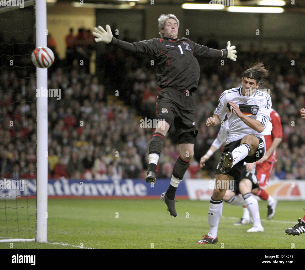 Germany?s Mario Gomez (2-R) is stopped by Wales? goalie Wayne Hennessey during the World Cup qualifying match Wales Stock Photo