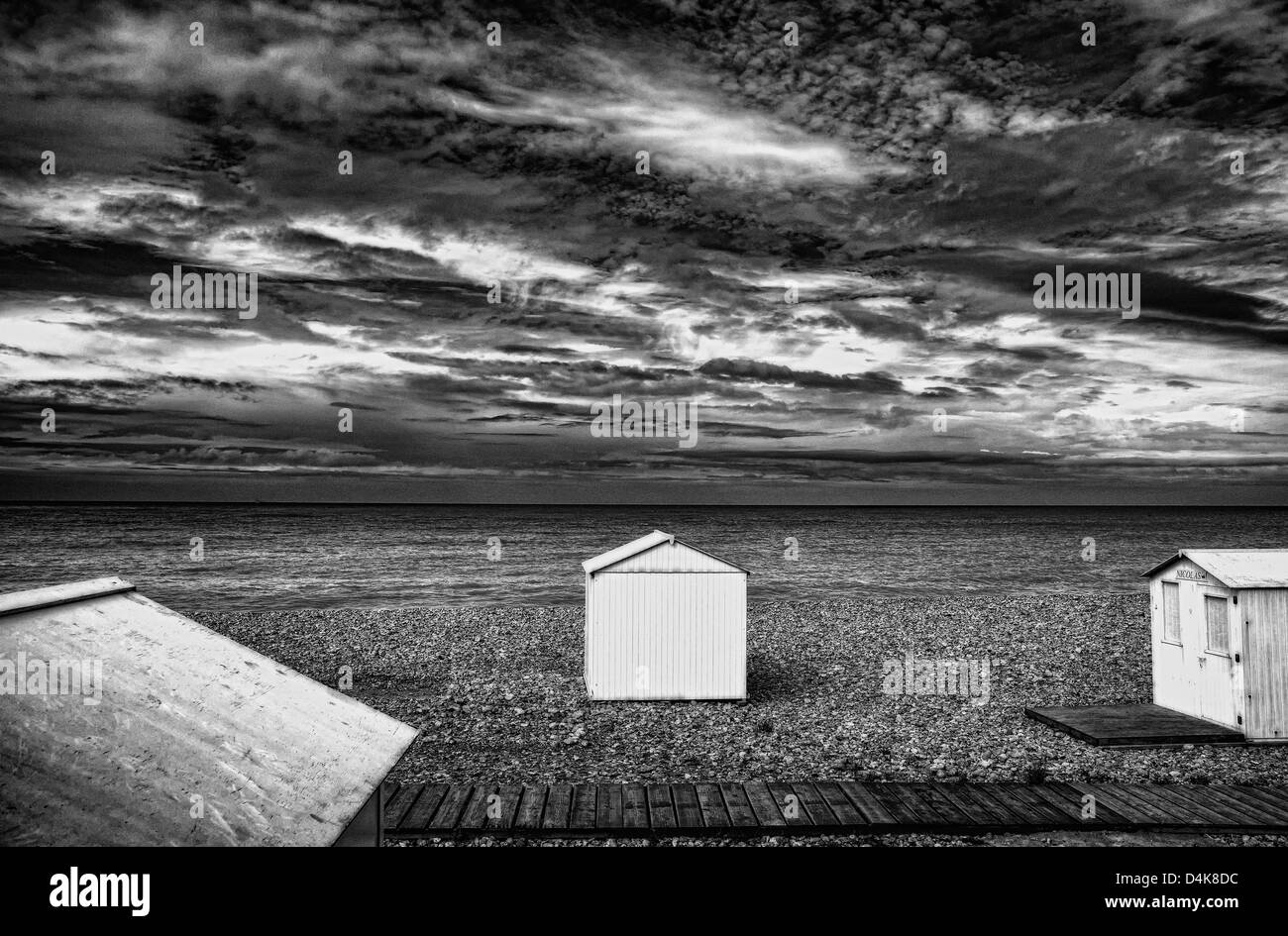 Huts on rocky beach - Stock Image