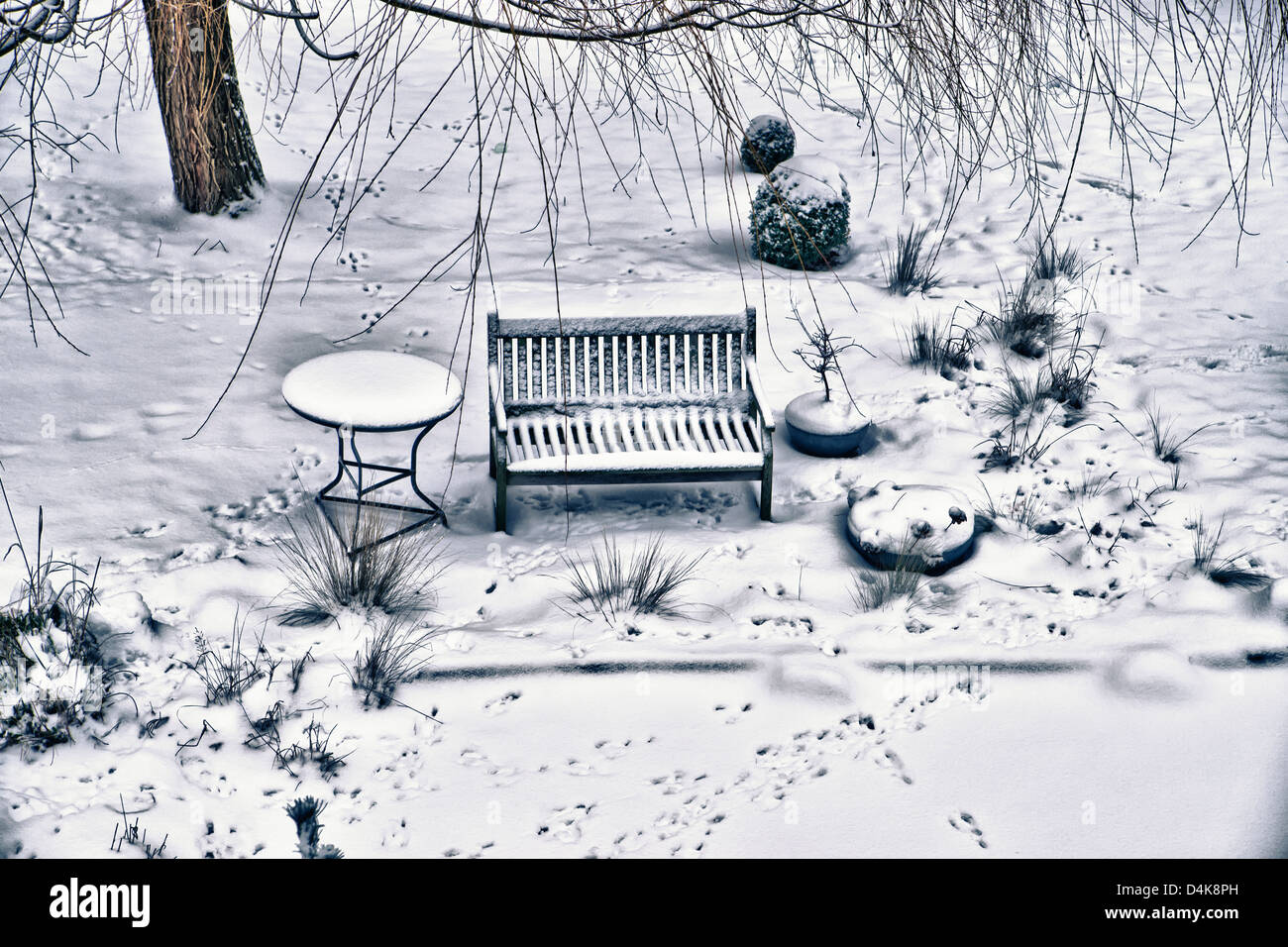 Bench and table on snowy street - Stock Image