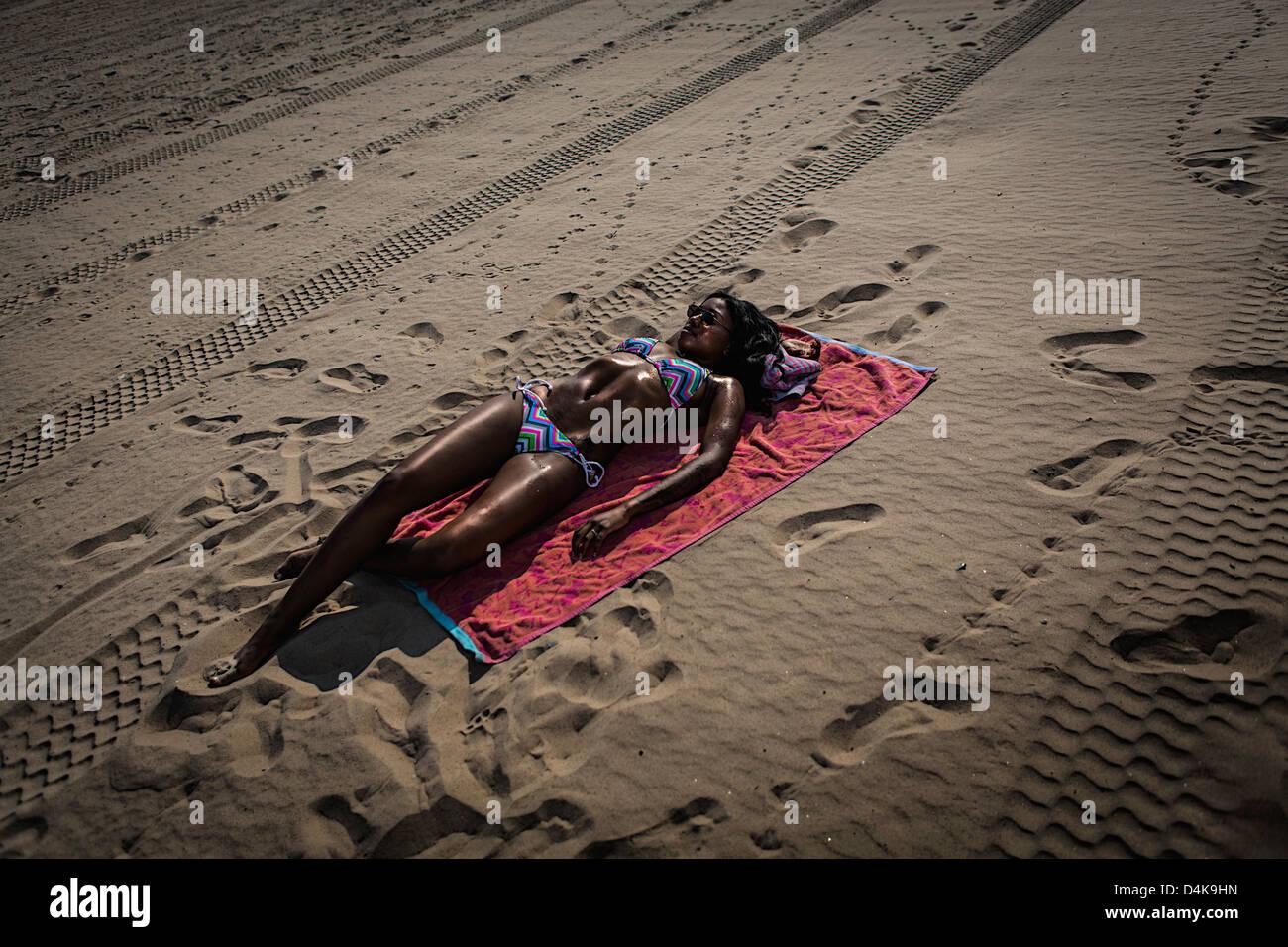 Woman sunbathing on towel on beach - Stock Image