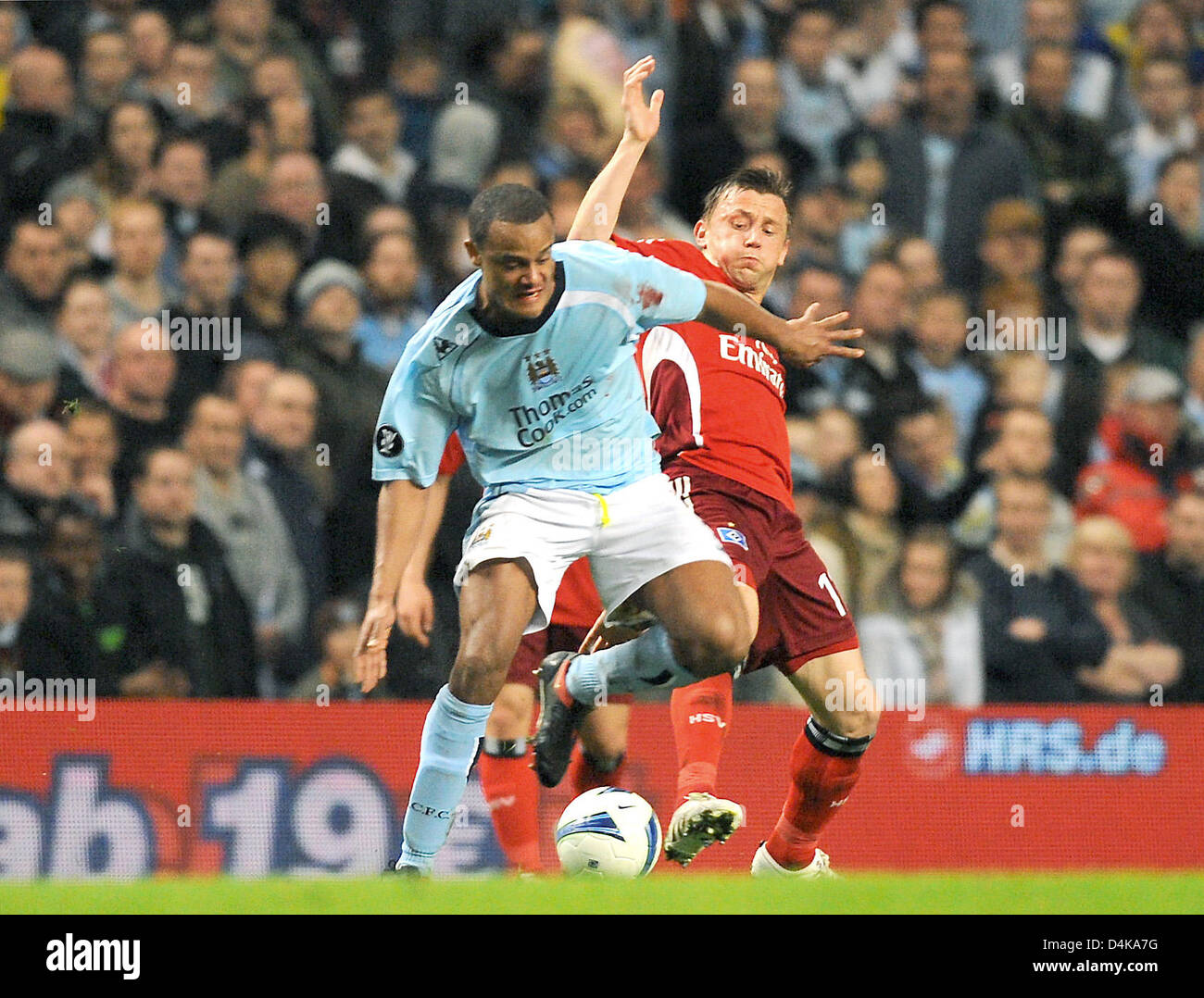 Manchester City?s Vincent Kompany vies for the ball with Hamburg?s Ivica Olic (R) during the UEFA Cup quarter finals Stock Photo