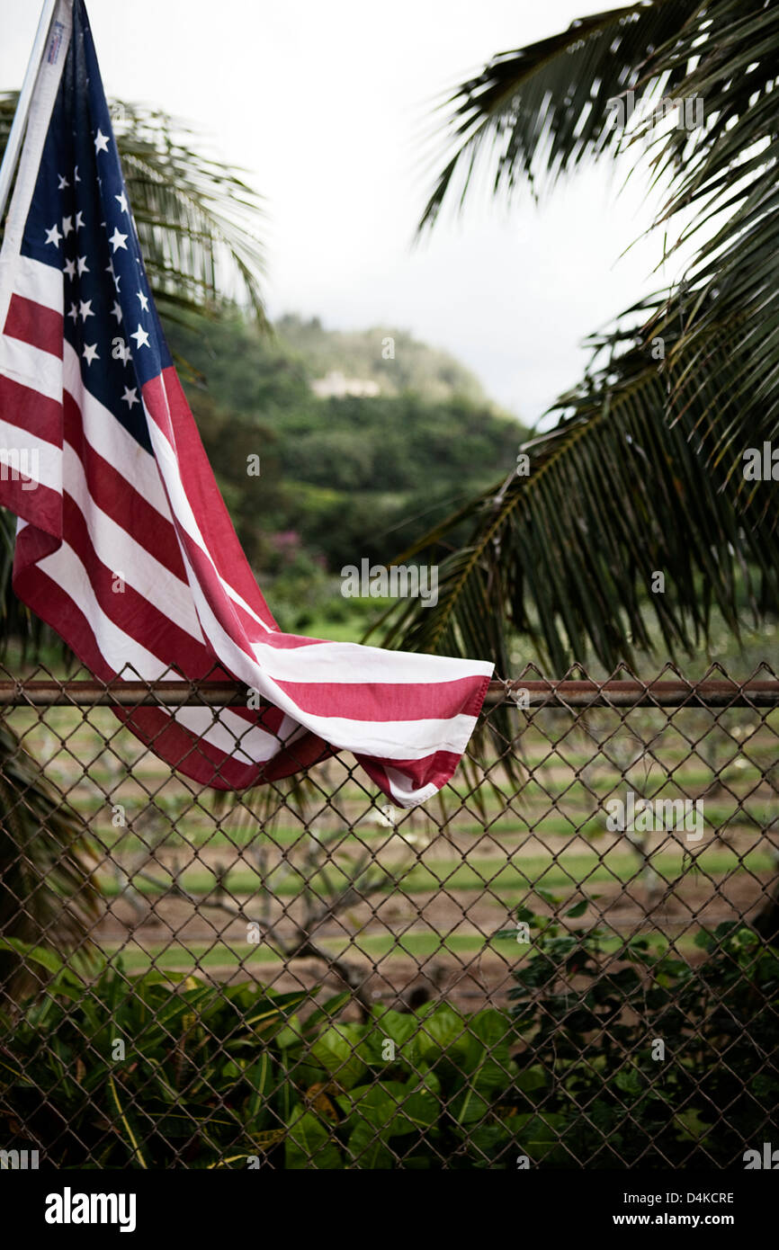 American flag hanging by chain fence - Stock Image